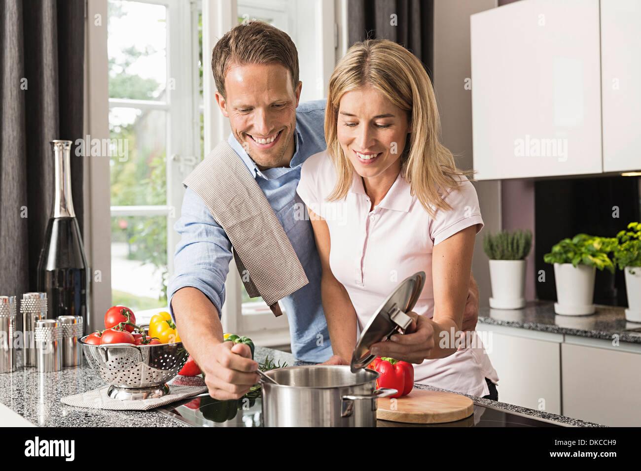 Mid adult couple preparing food - Stock Image