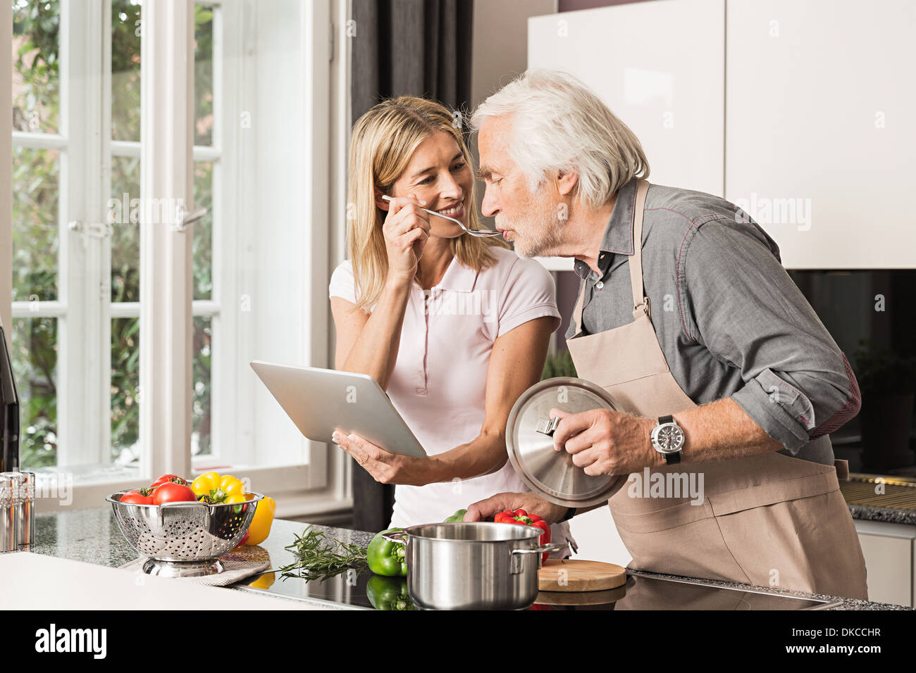 Senior man cooking with daughter, tasting food - Stock Image