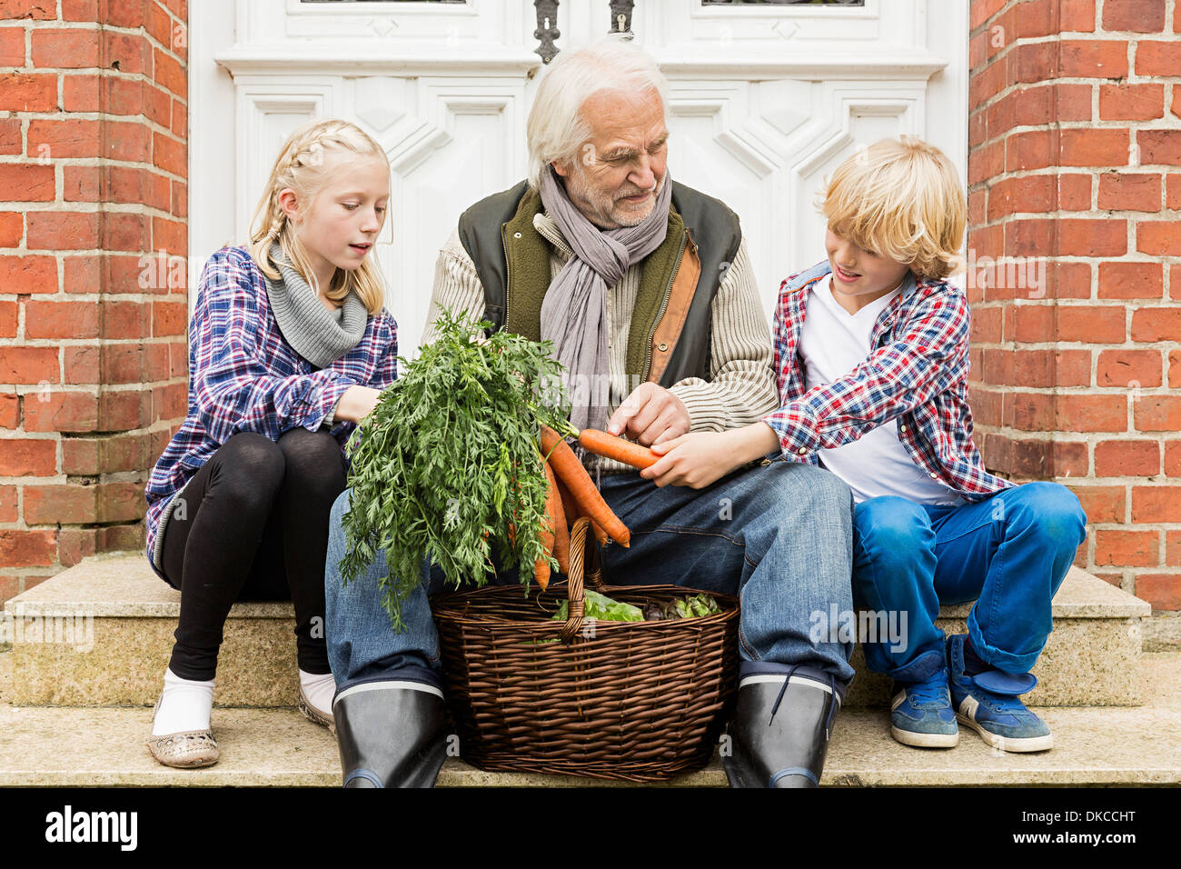 Grandfather sitting with grandchildren on doorstep with carrots - Stock Image