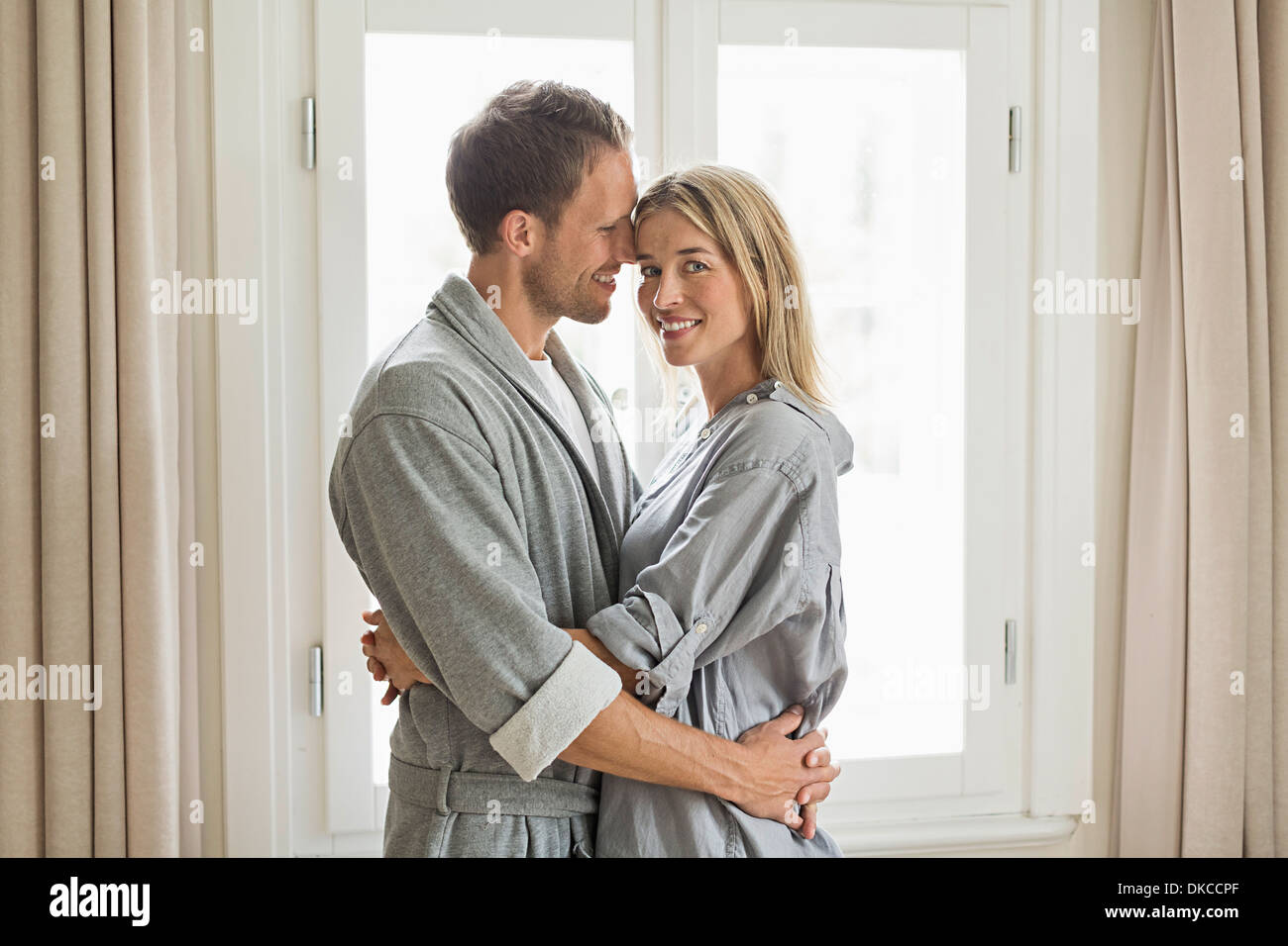 Portrait of mid adult couple wearing dressing gowns, hugging - Stock Image