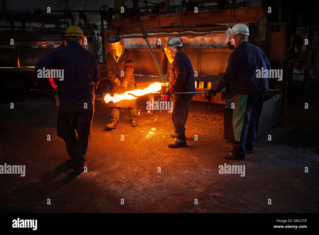 Red hot steel billet which has already been partially pre formed is moved back in to the furnace - Stock Image
