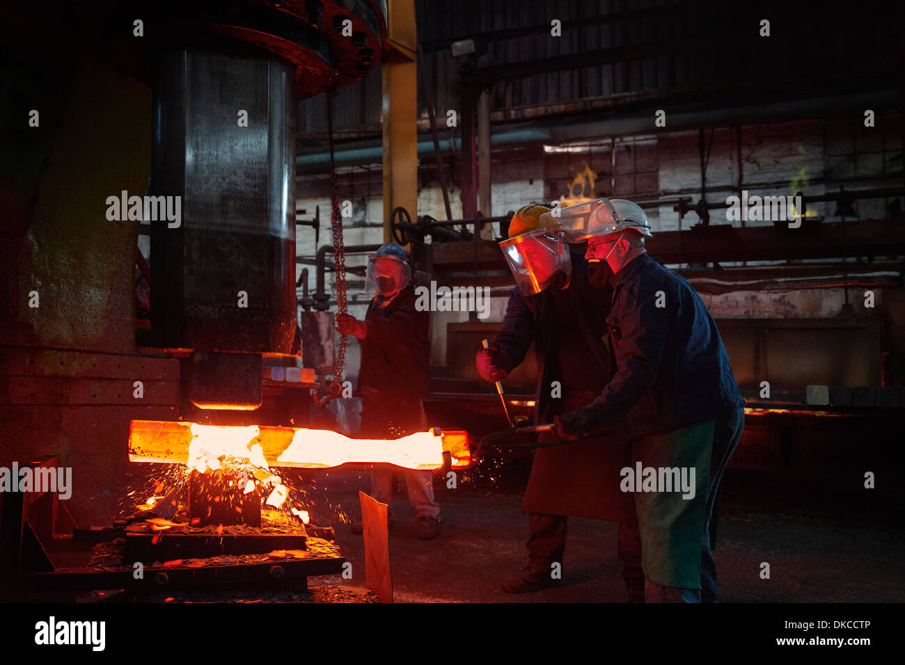 Forge workers pre form red hot steel billet into flight bar (mining component) on hammer - Stock Image