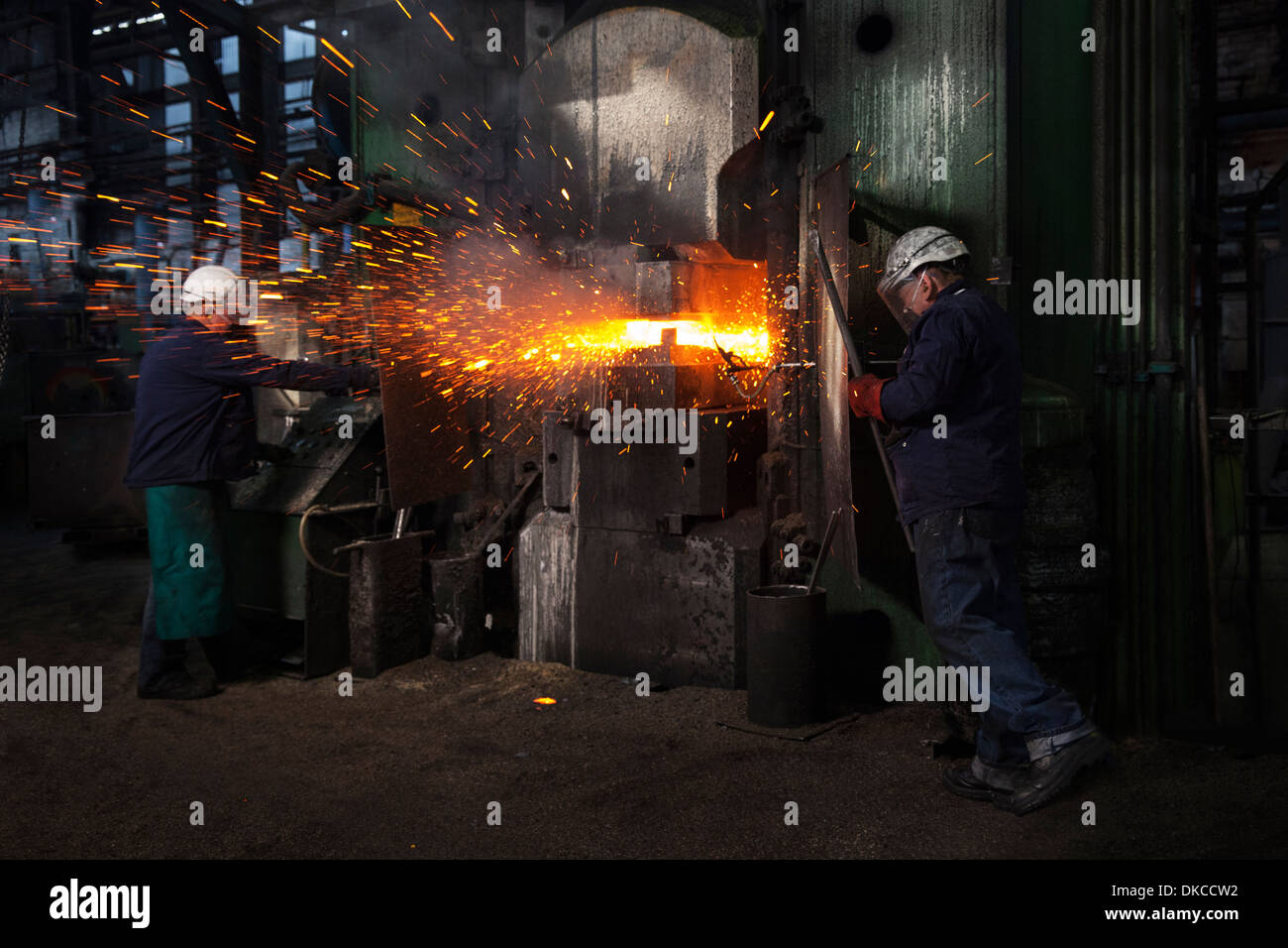 Sparks fly as counterblow hammer forms flight bar, the counterblow hammer forges by striking from both above and below - Stock Image