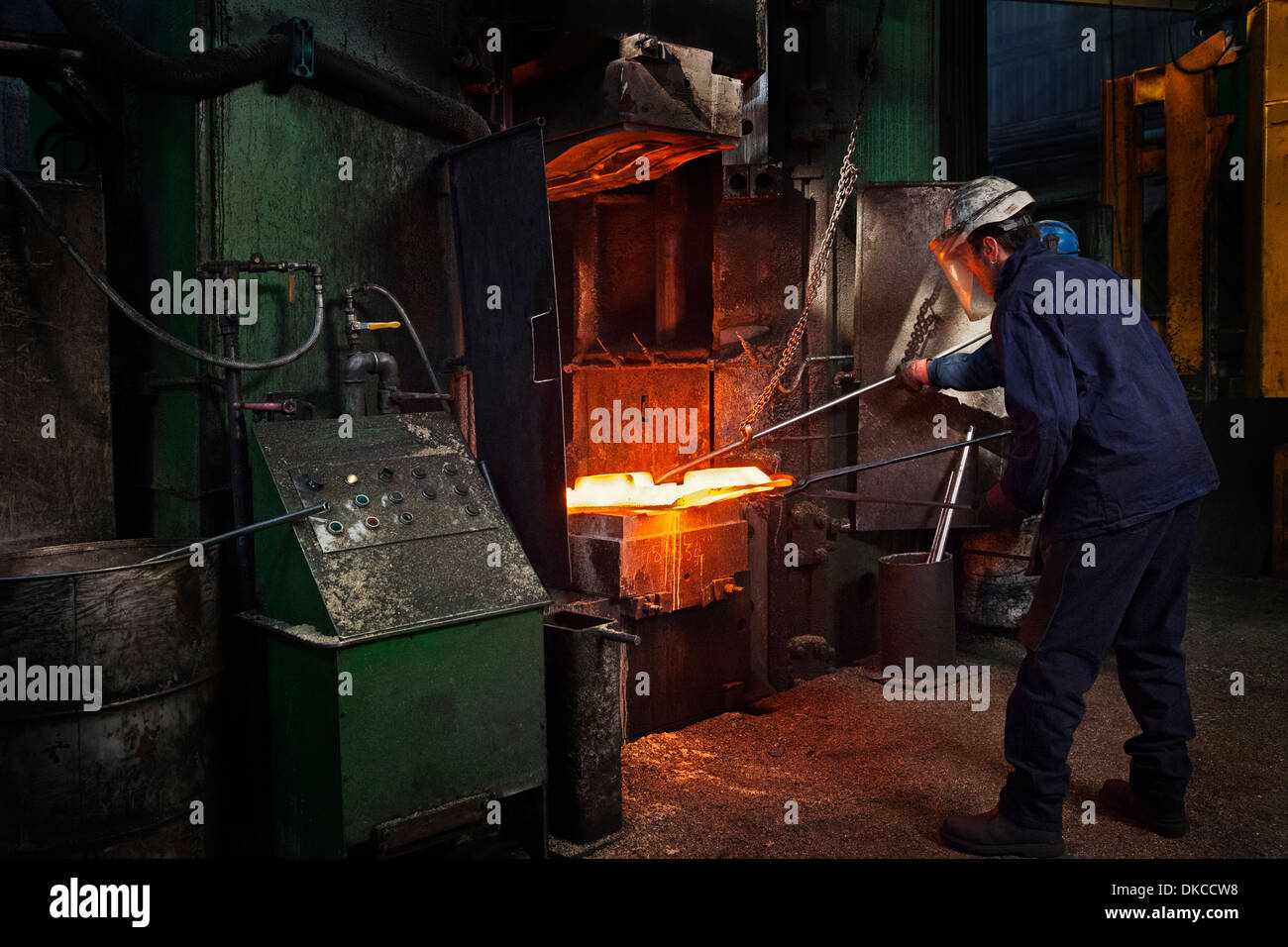 Flight bar (mining component) having been forged in big hammer, is levered off the counterblow hammer - Stock Image
