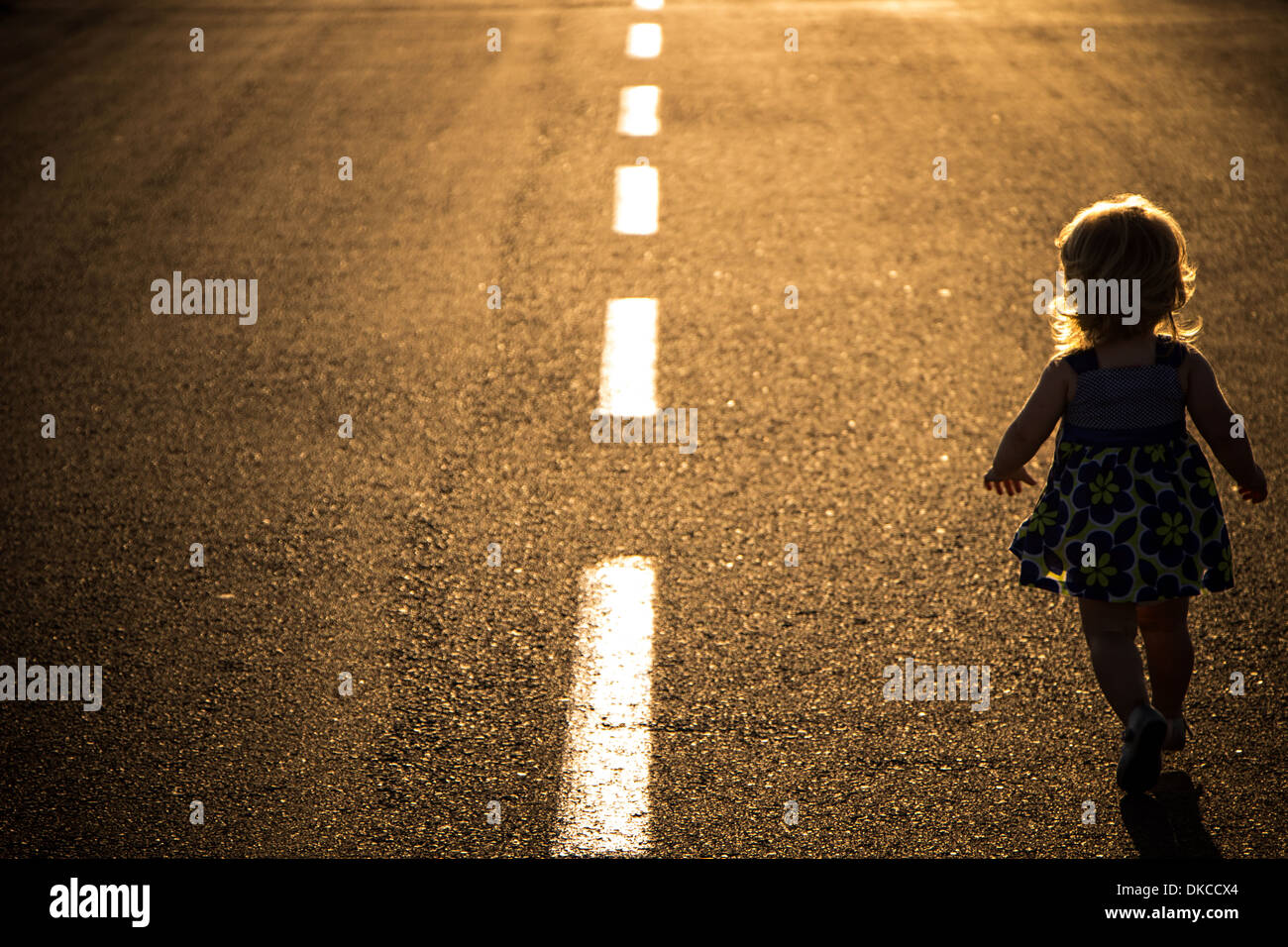Little girl running away on the road ahead - Stock Image