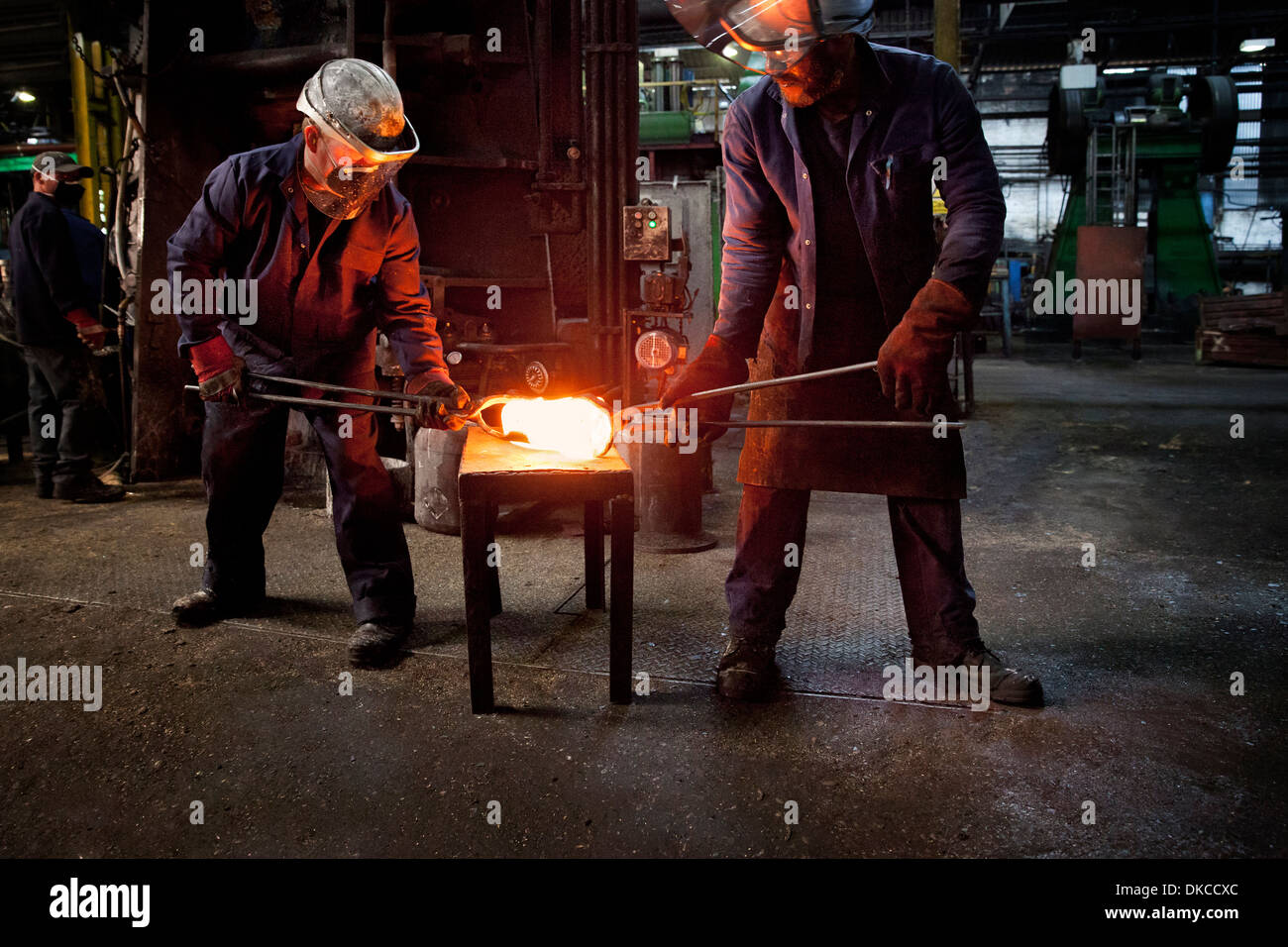 Worker hands over pre formed steel billet for presentation to set of two dies in hammer to be fully forged into crank shaft - Stock Image