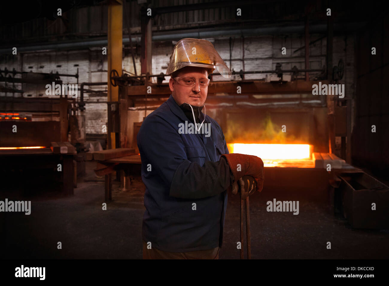 Forge worker, second in command of hammer control or 'stamper' in pre forming forging area with a set of industrial tongs - Stock Image