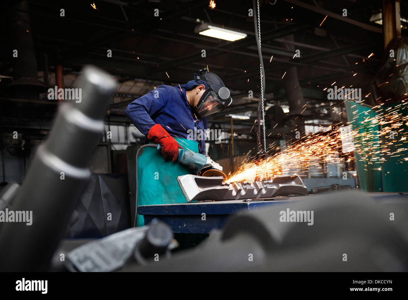Worker grinding (linishing) flight bar (mining component), removing last traces of excess flash not removed by clipping press - Stock Image