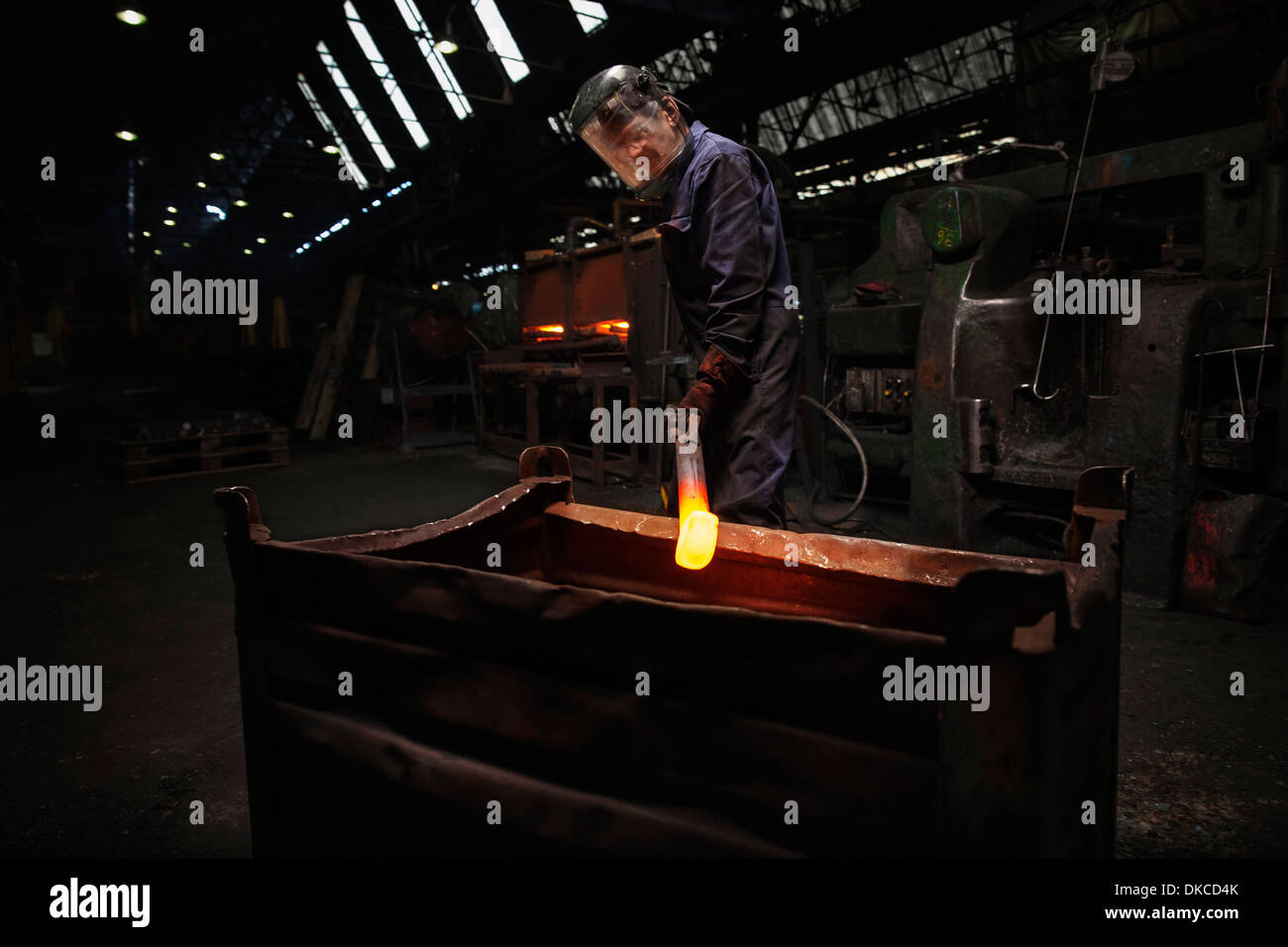 Forge worker preparing to release finished upset forging into steel container - Stock Image