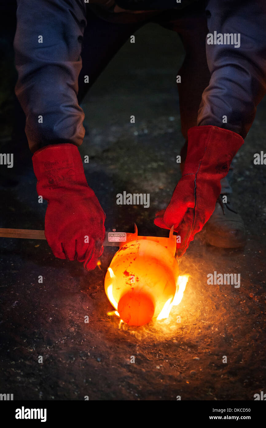 Checking diameter of a still red hot flaming crank shaft with a vernier - Stock Image