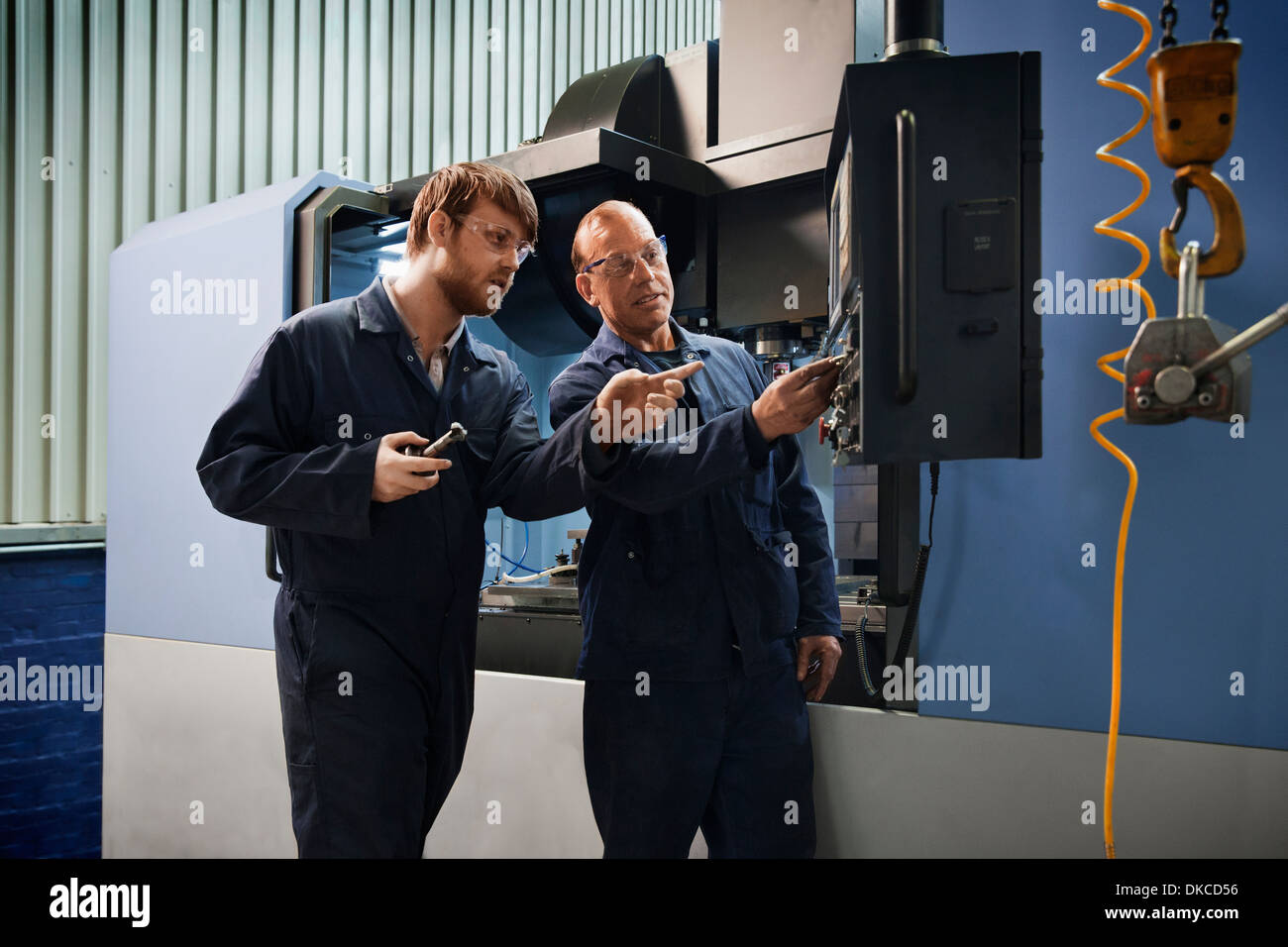 An experienced worker explains the workings of a CNC machine to an apprentice - Stock Image