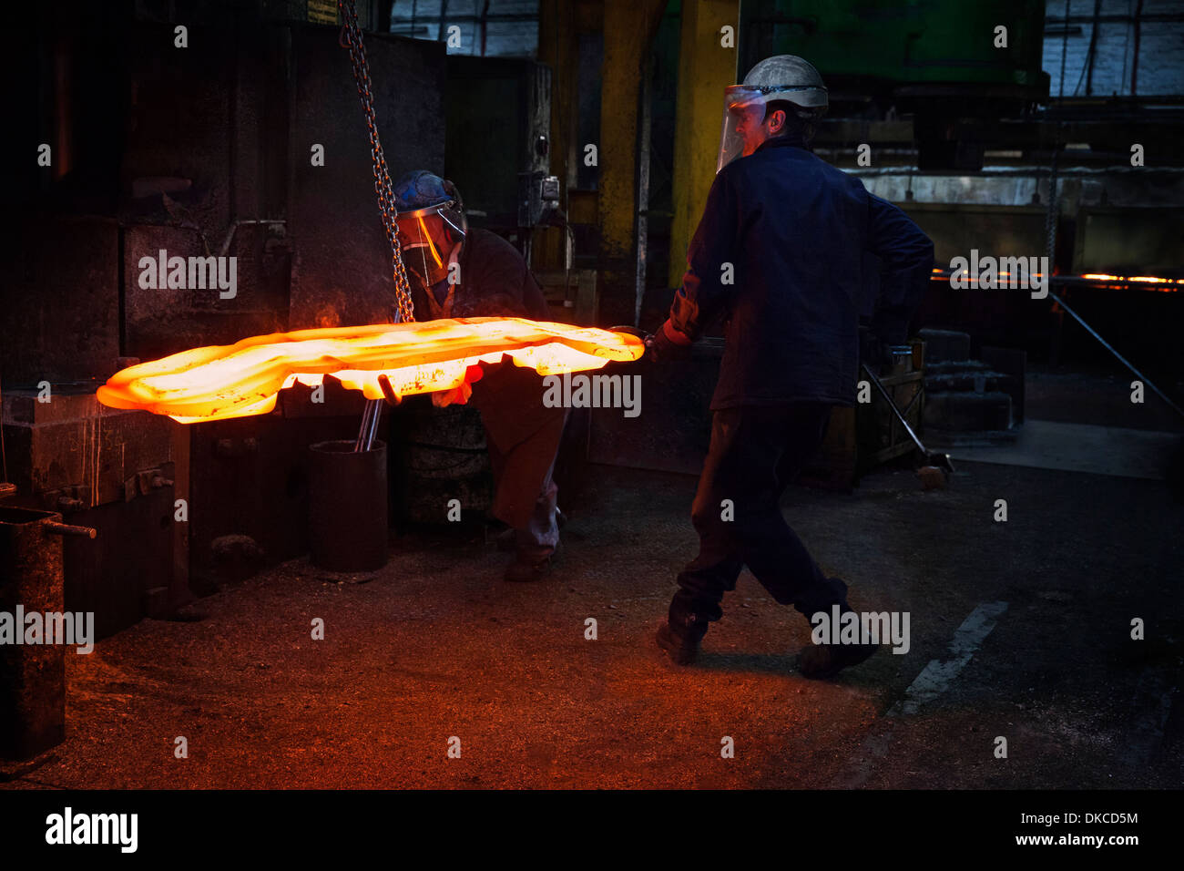 Flight bar having been forged in a 15 MT counterblow hammer, is moved to clipping press to clip off excess 'flash' - Stock Image