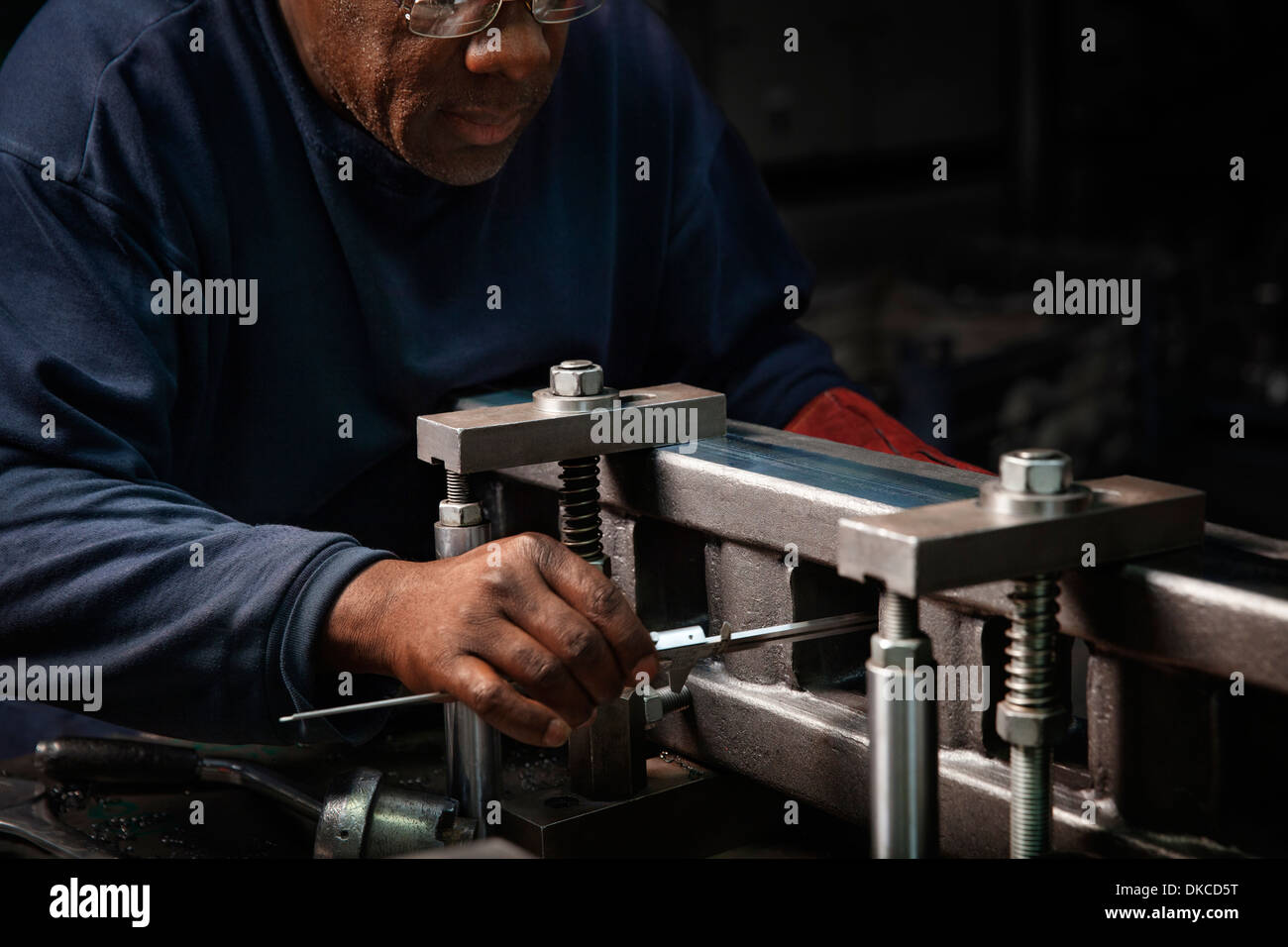 Worker setting up a rack bar to be machined - Stock Image
