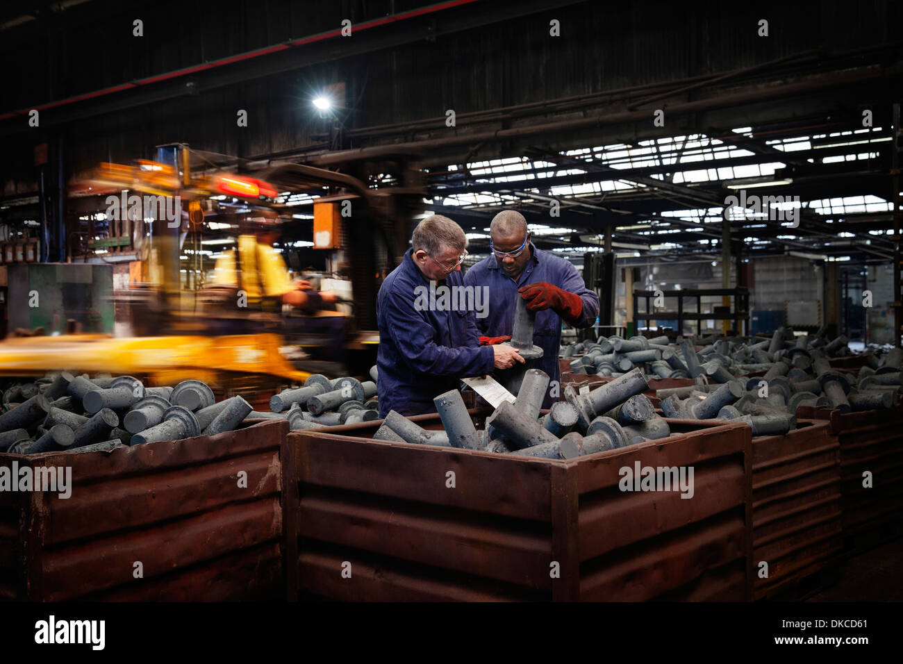 Checking dimensions on crank shafts in warehouse area, fork lift truck unloads a new steel container of product in background - Stock Image
