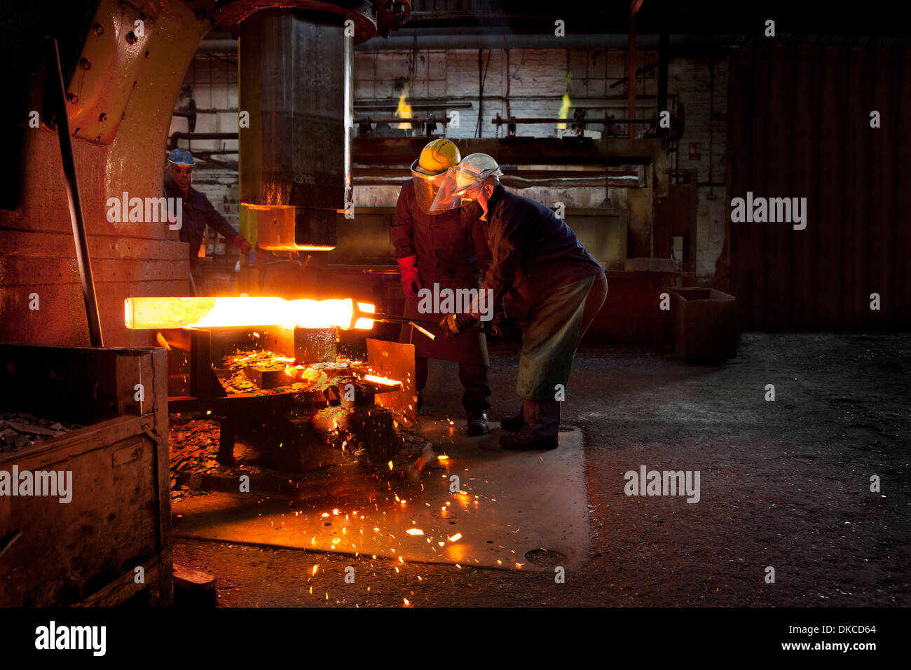 Forge workers pre form red hot billet into flight bar (mining component) on hammer - Stock Image