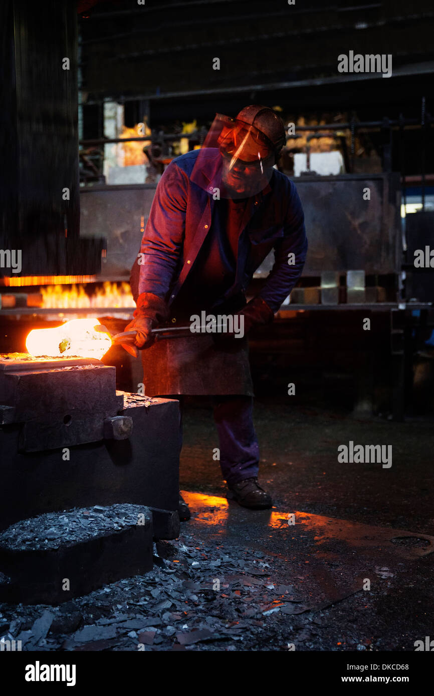 Worker pre forms steel billet on 5 tonne clear space hammer to be presented to set of two dies to be fully forged in hammer - Stock Image