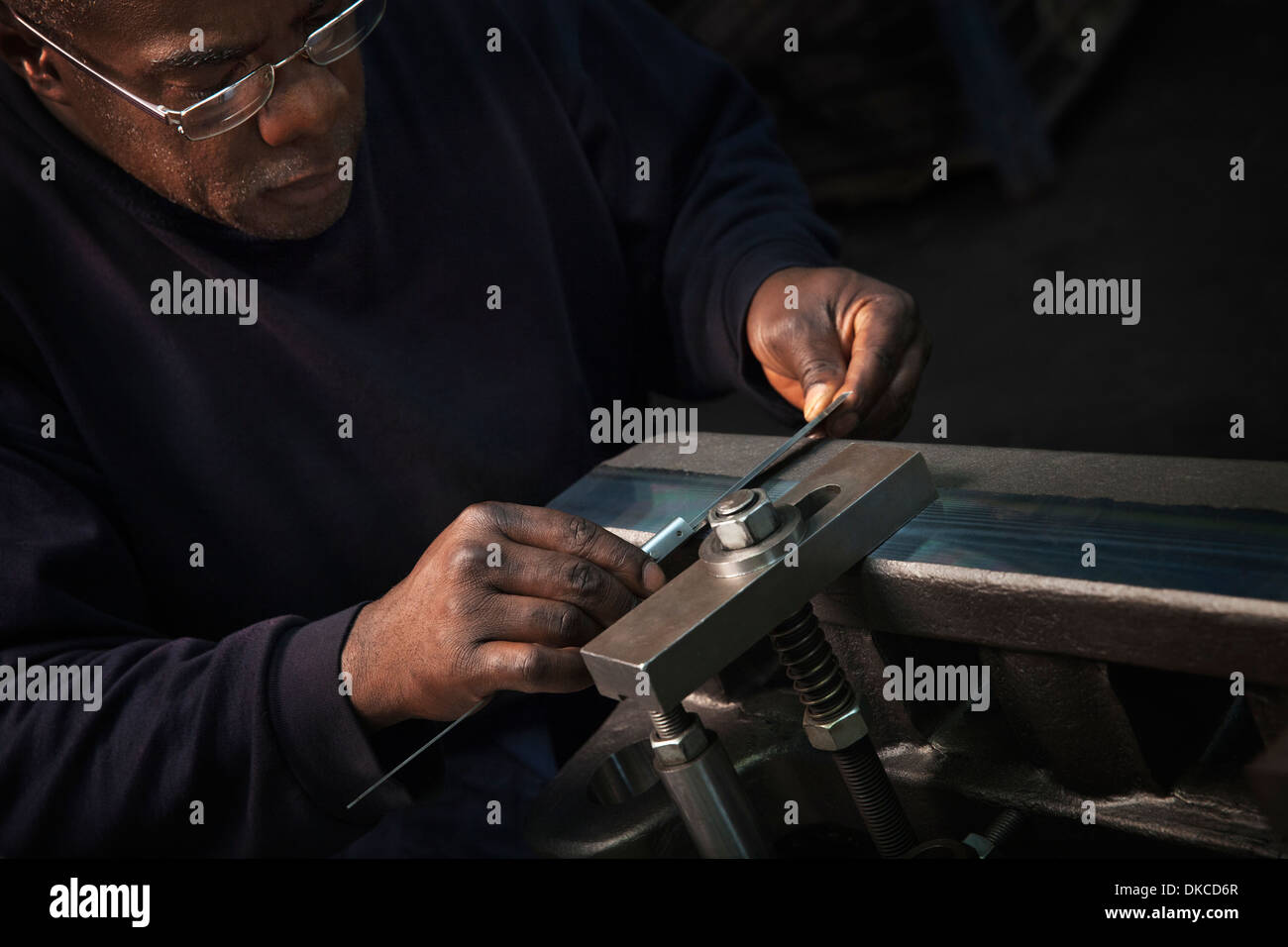 Checking rack bar with a vernier in preparation for further machining - Stock Image