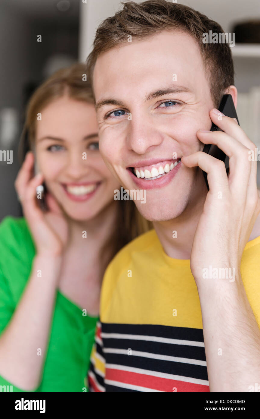 Young man on cell phone with woman in background Stock Photo