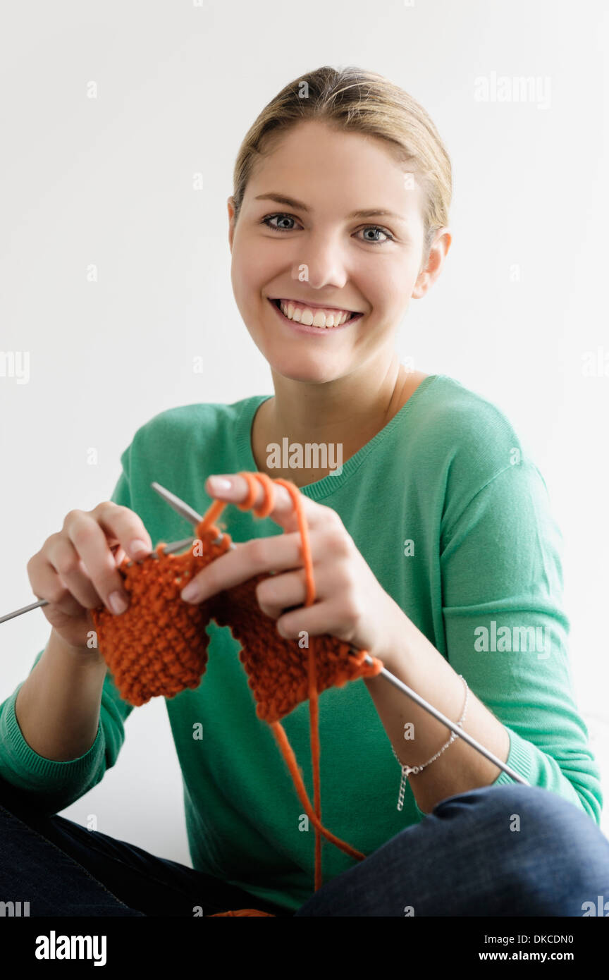 Portrait of young woman knitting - Stock Image