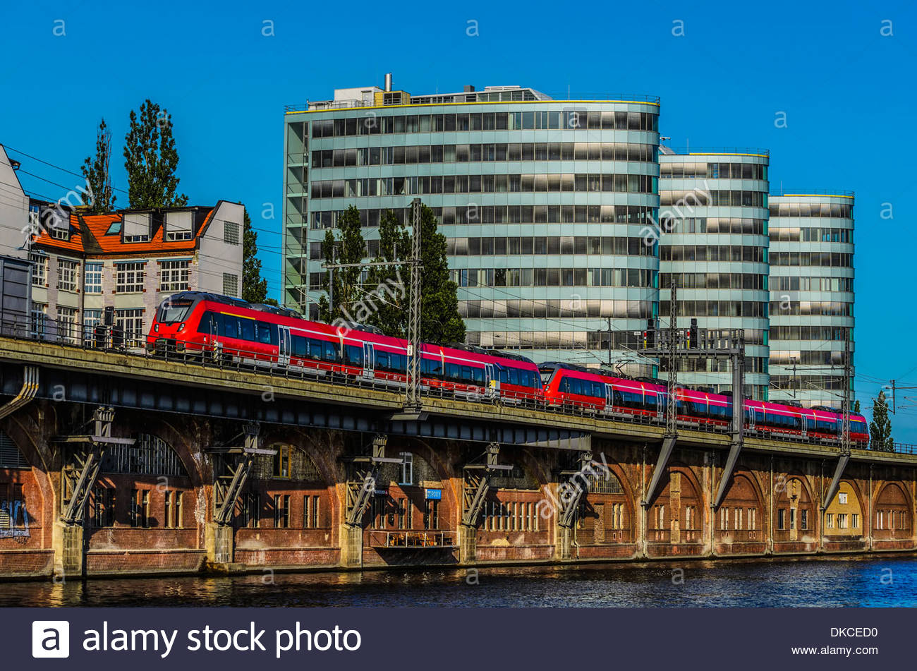 Commuter train along Spree River with office buildings, Berlin, Germany - Stock Image