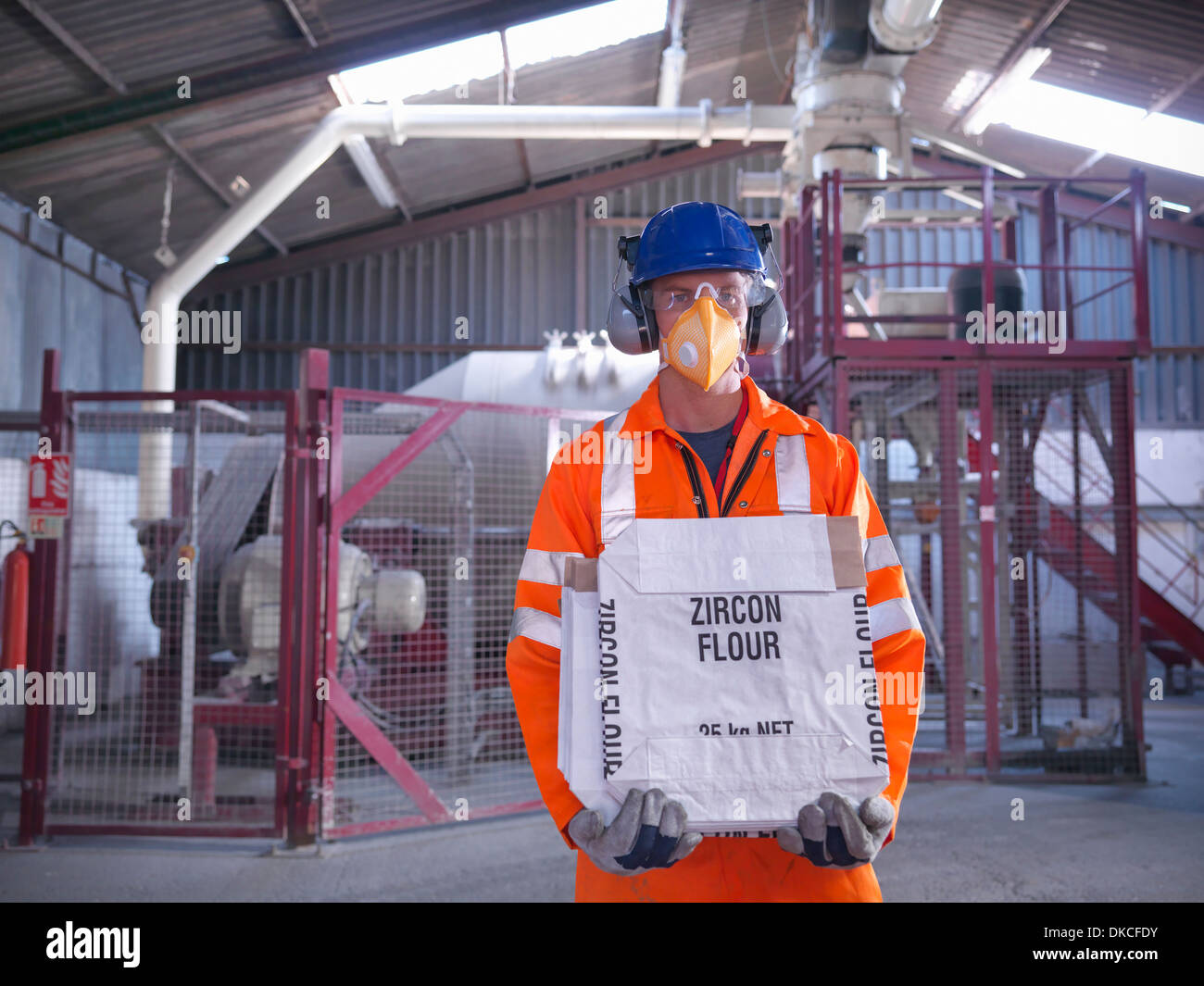 Worker in protective clothing holding zircon flour bag in mill - Stock Image