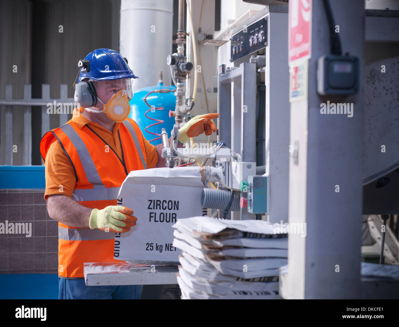 Worker in protective clothing filling zircon flour bags in mill - Stock Image