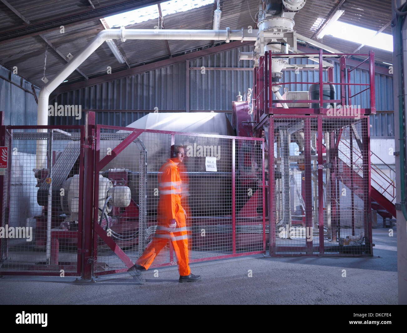 Worker in reflective clothing passing machinery in zircon flour mill - Stock Image