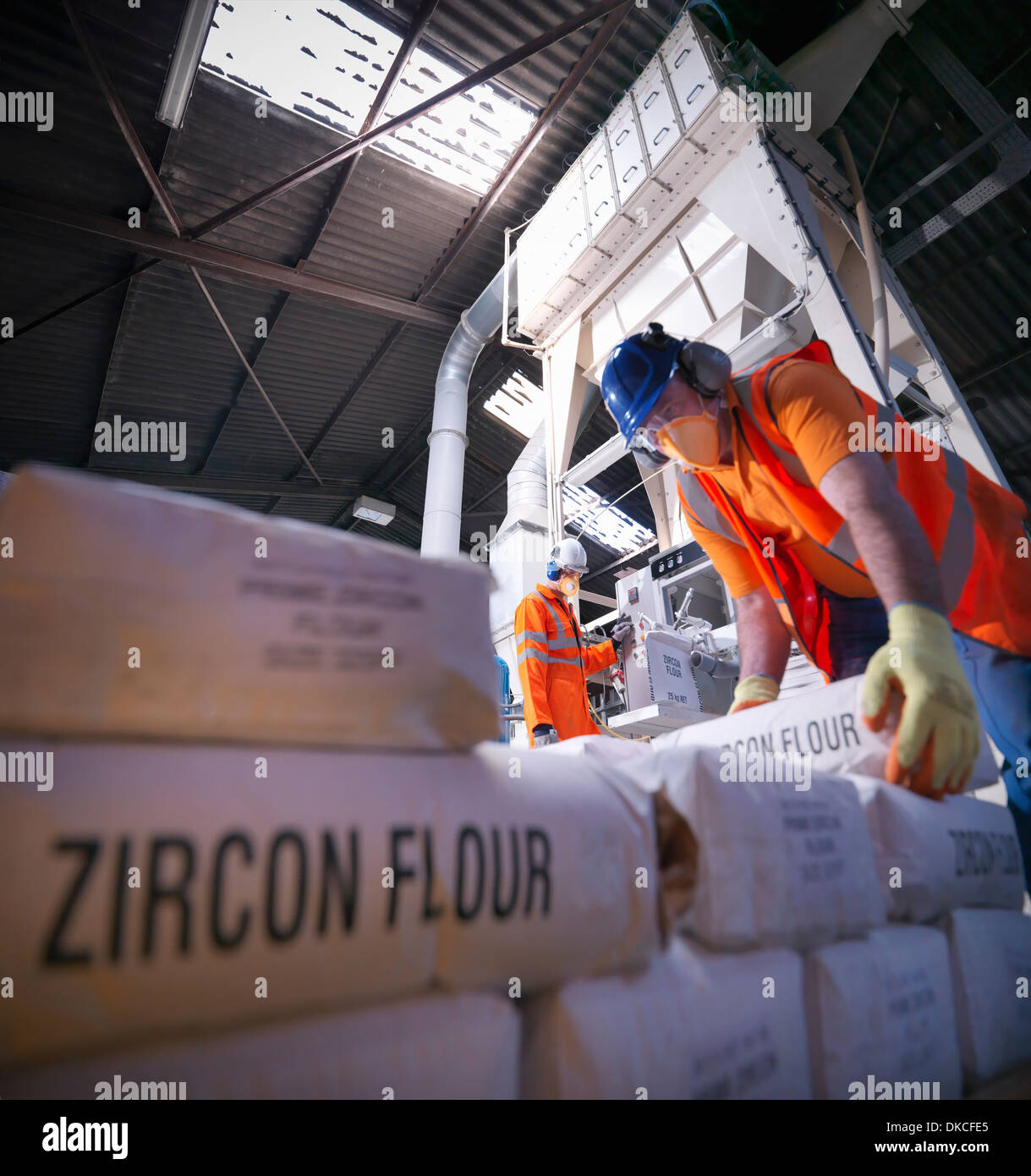 Workers in protective clothing filling zircon flour bags in mill, low angle view - Stock Image