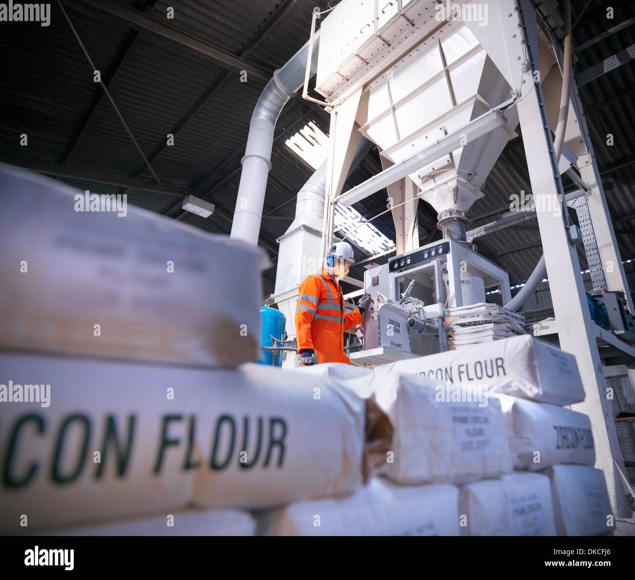 Worker in protective clothing filling zircon flour bags in mill, low angle view - Stock Image