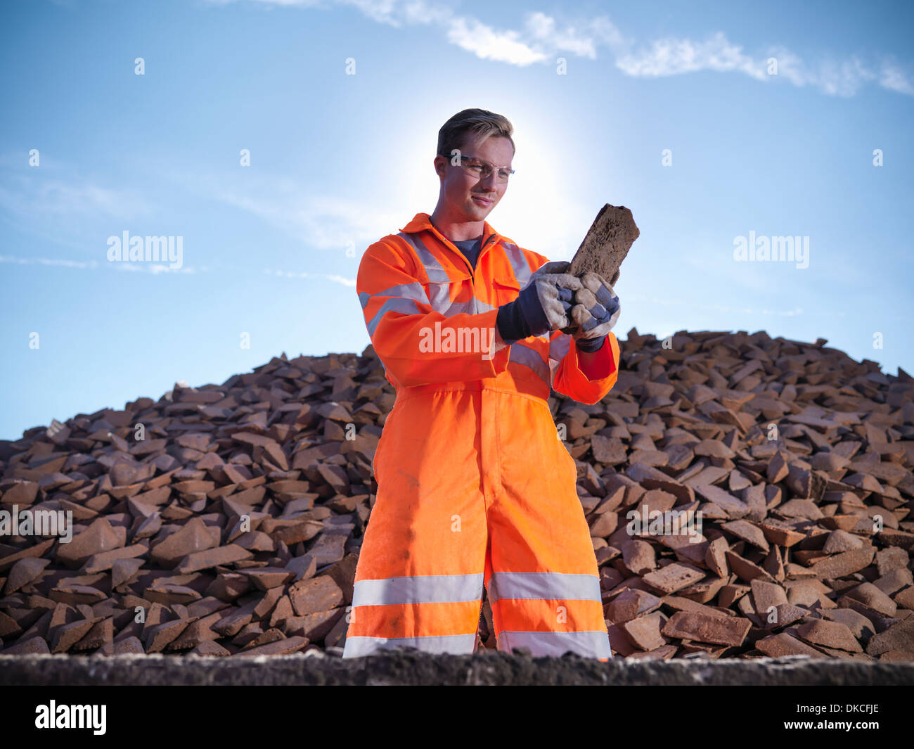 Worker in reflective clothing inspecting pig iron - Stock Image