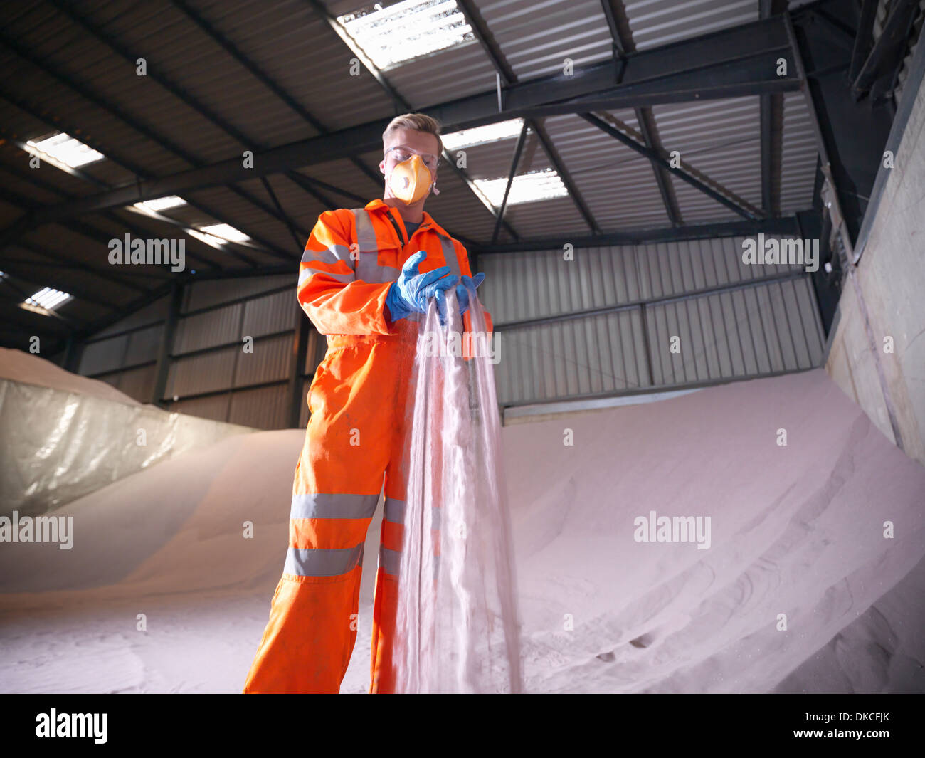 Worker in reflective clothing inspecting zircon sand - Stock Image