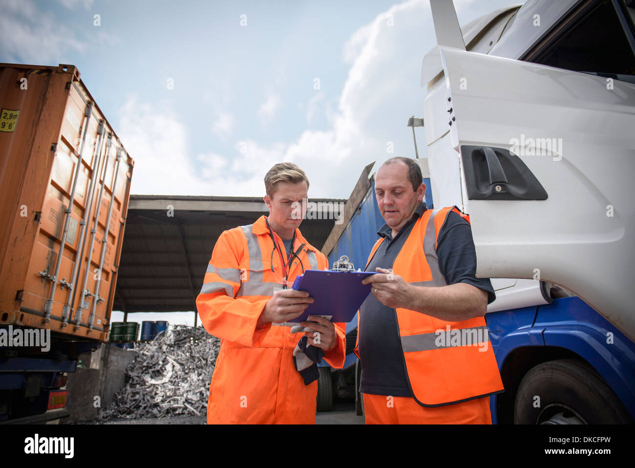 Worker inspecting delivery paperwork with truck driver - Stock Image