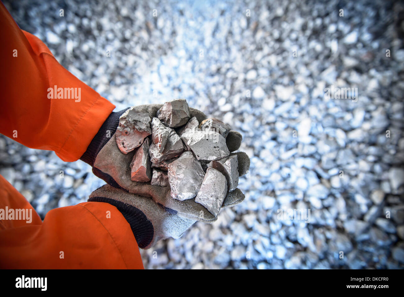 Close up of workers hands holding crushed titanium - Stock Image