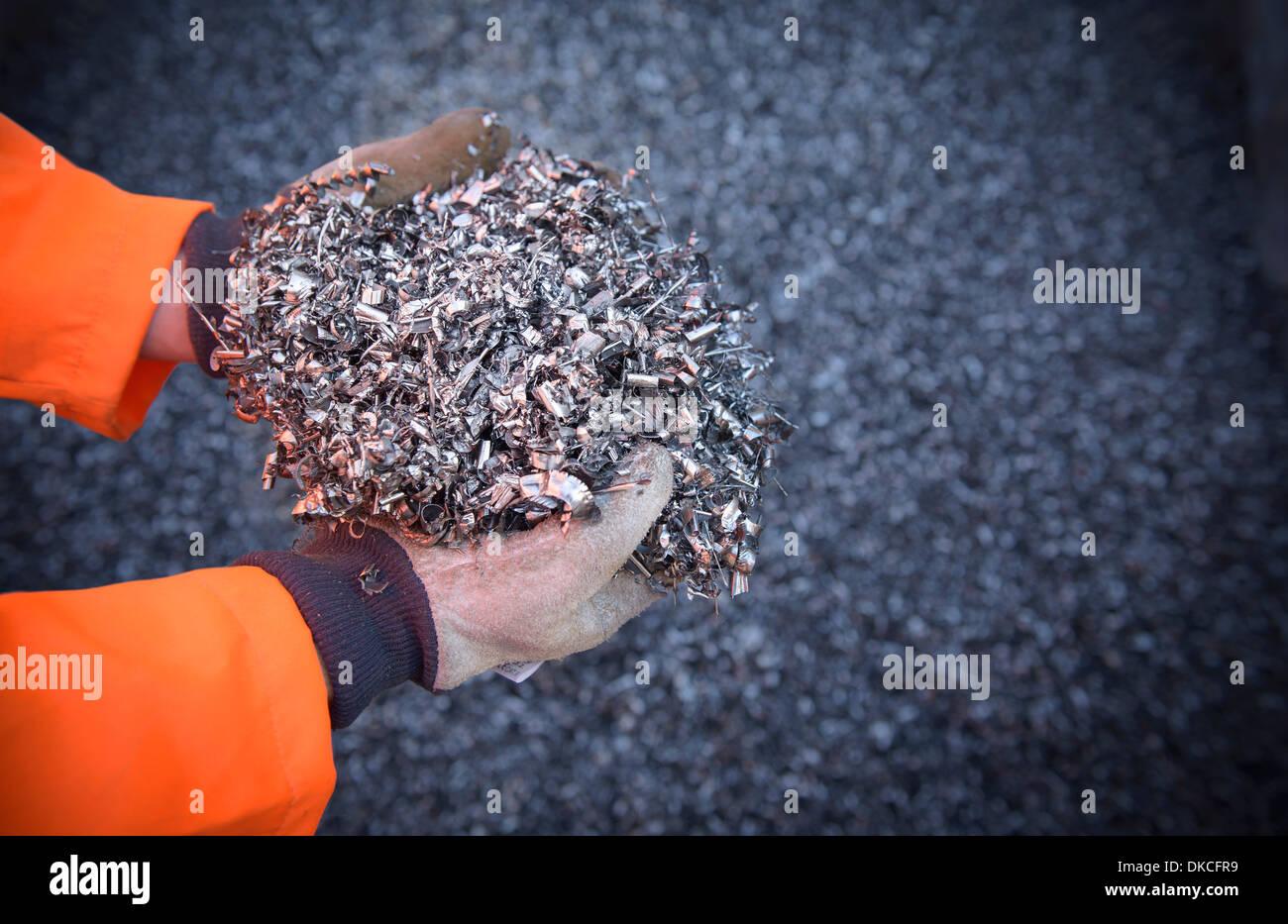 Close up of worker holding titanium turnings - Stock Image