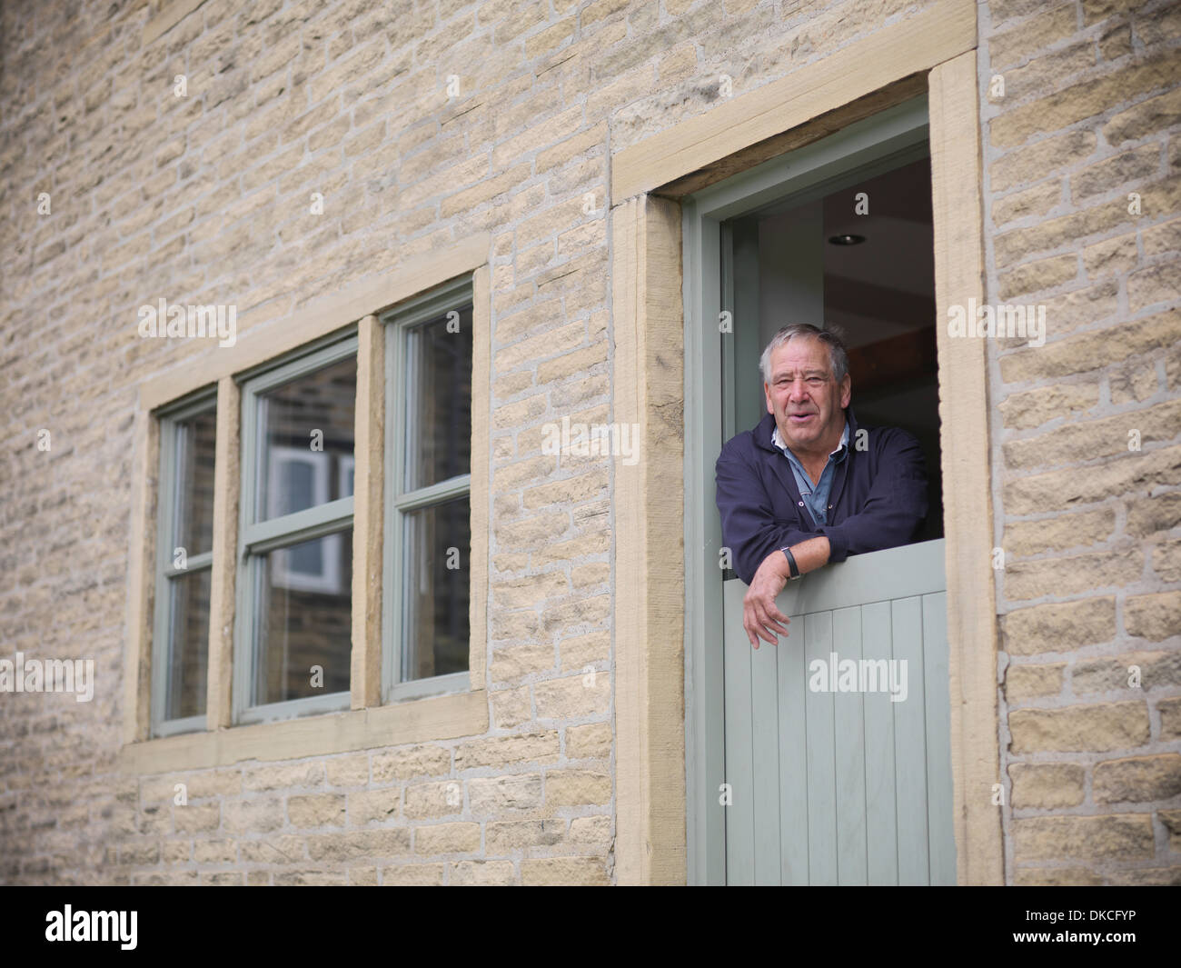Portrait of mature farmer looking out from farmhouse door - Stock Image
