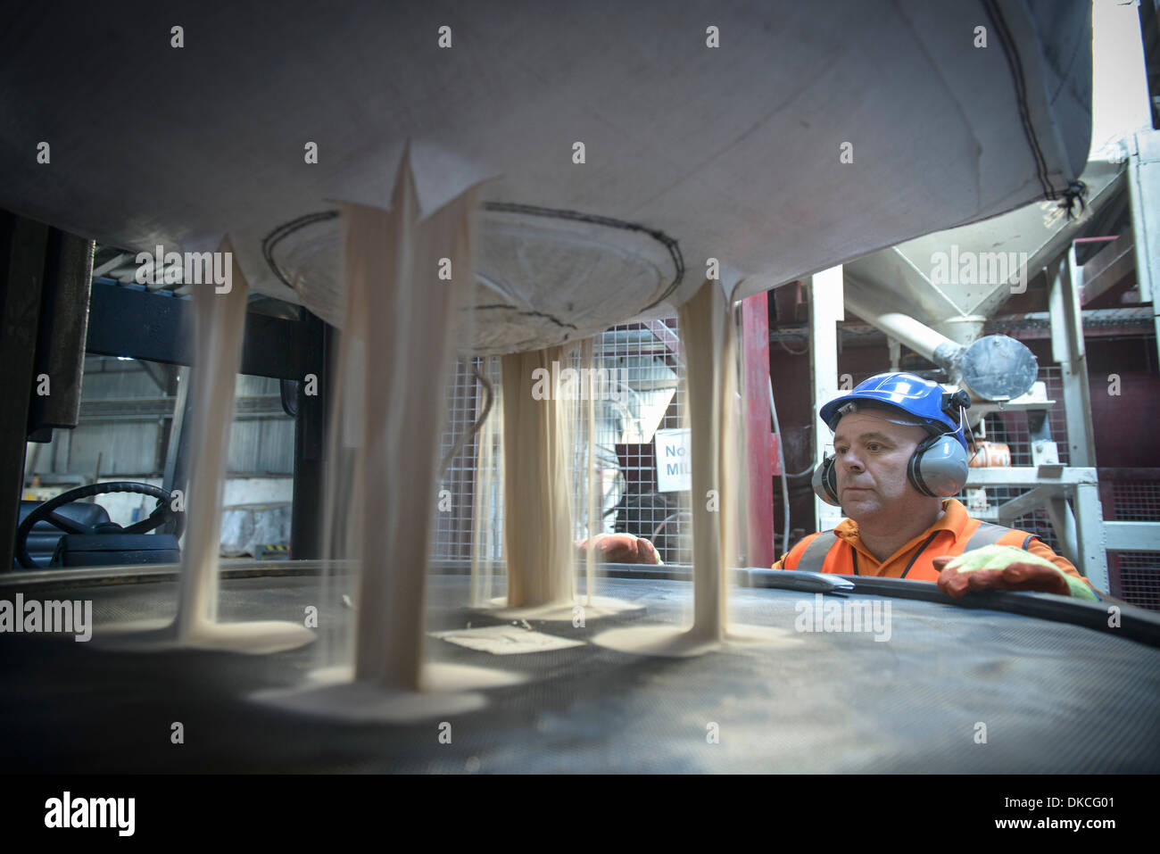 Worker in hard hat and ear defenders inspecting zircon sand - Stock Image