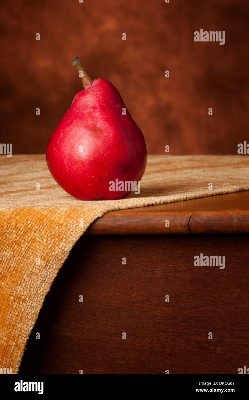 A single red anjou pear sits atop an antique table on a gold woven cloth. This photo has warm shades of red, brown, and gold and - Stock Image