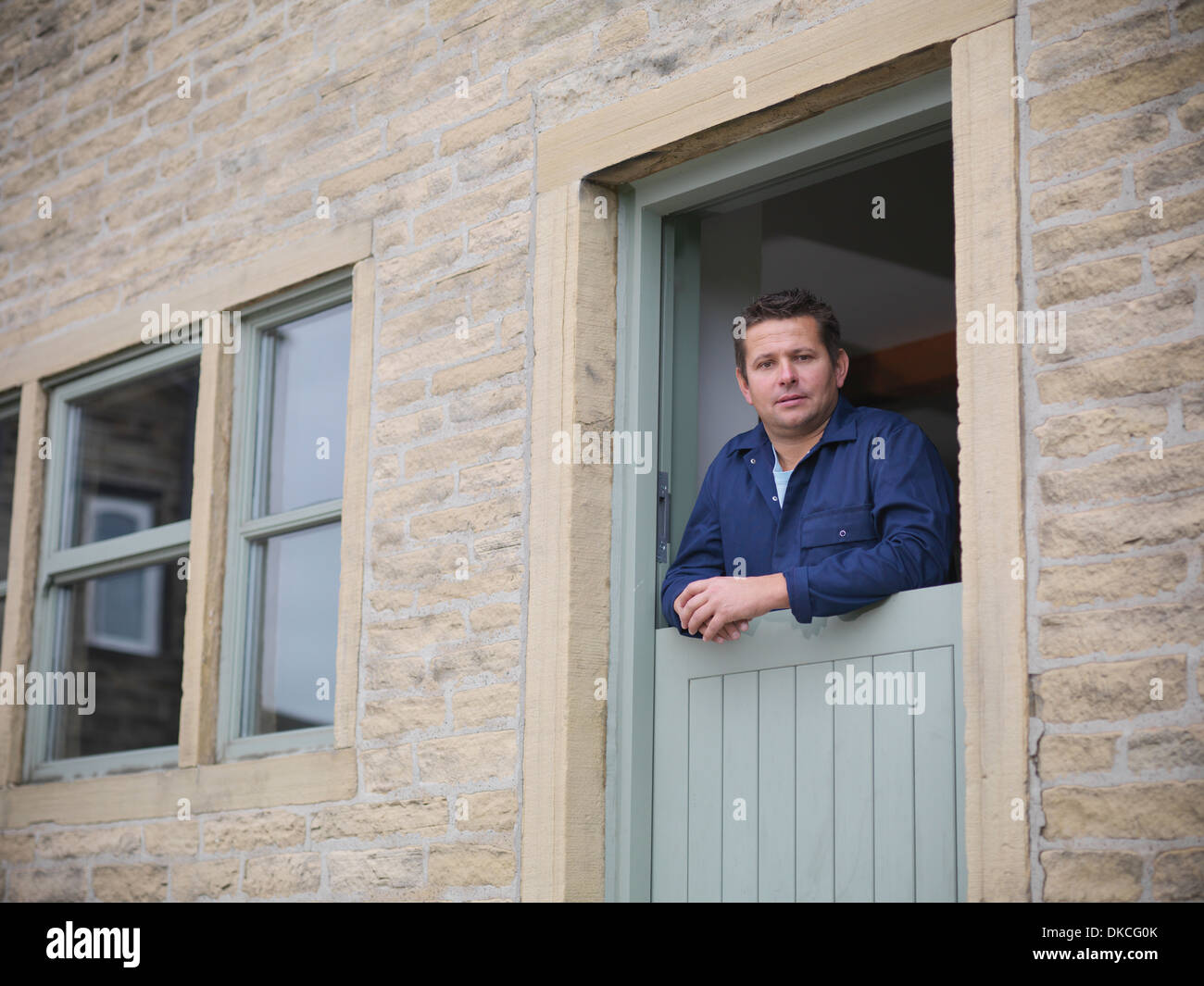 Portrait of farmer looking out from farmhouse door - Stock Image