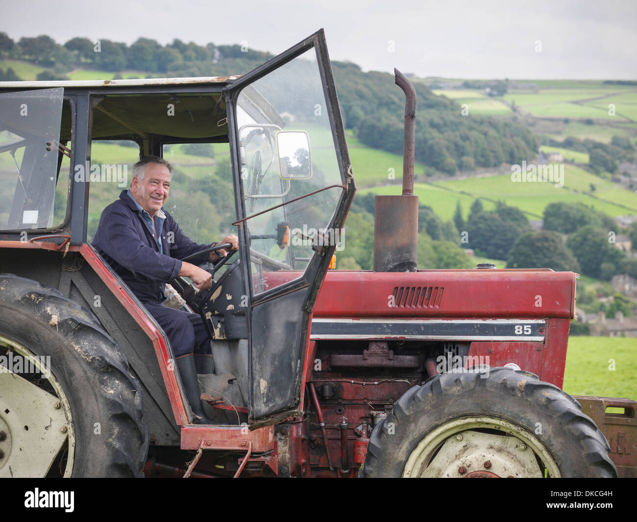 Mature farmer smiling in tractor - Stock Image