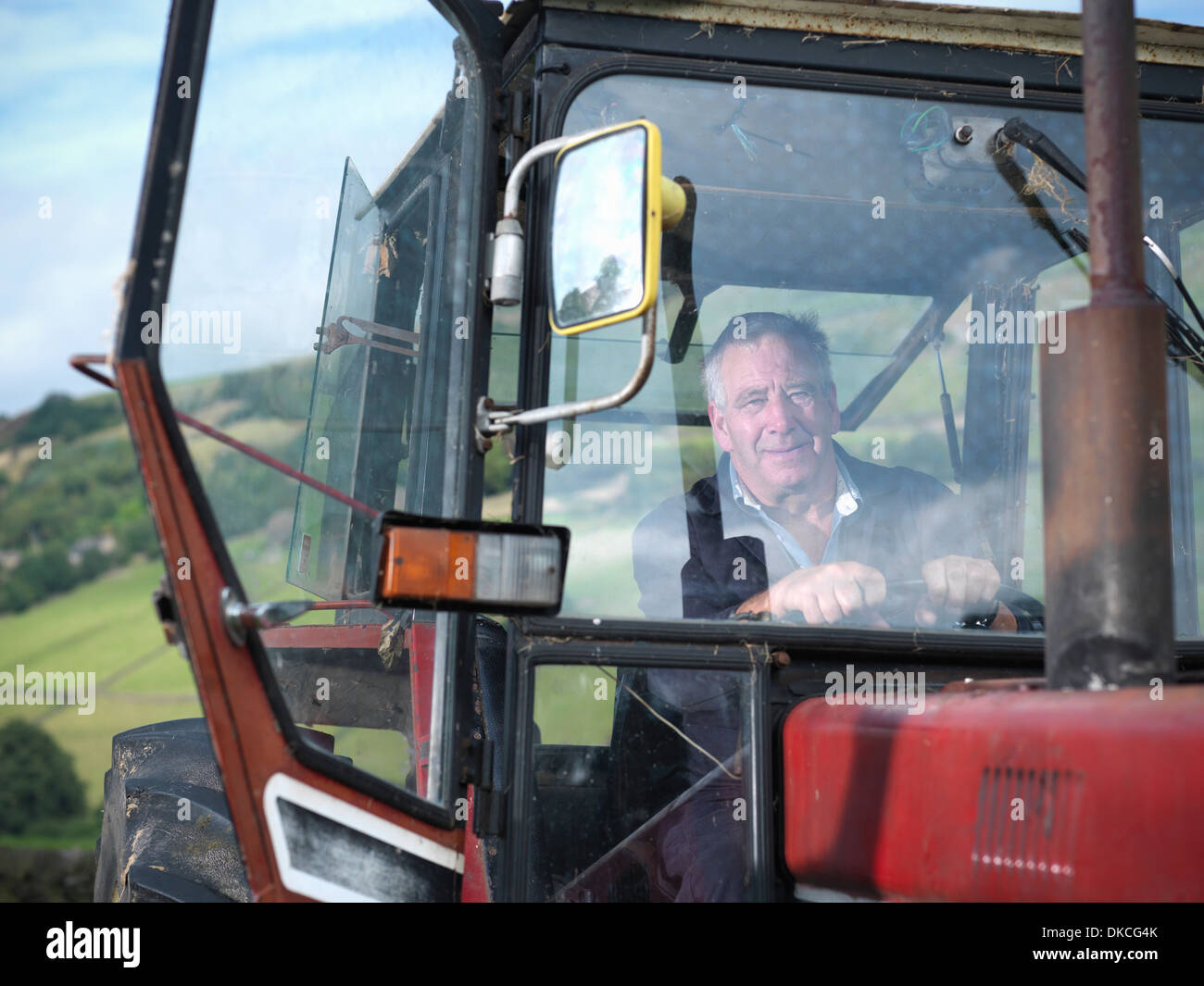 Mature farmer in tractor cab, portrait - Stock Image