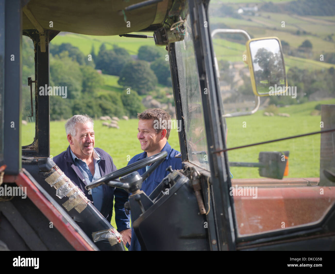 Farmer and son talking next to tractor in field Stock Photo