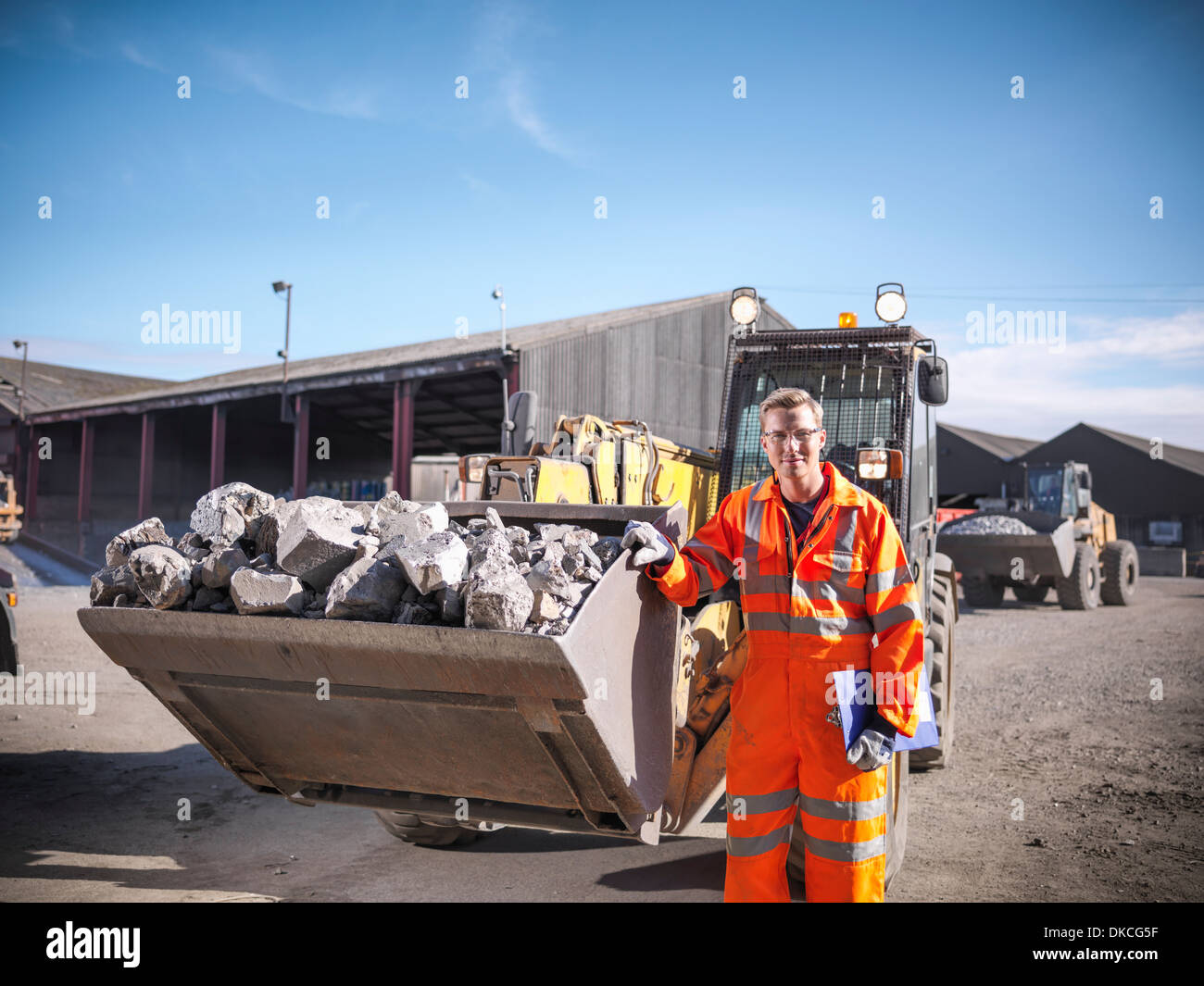 Portrait of worker in reflective workwear with dumper of crushed titanium - Stock Image