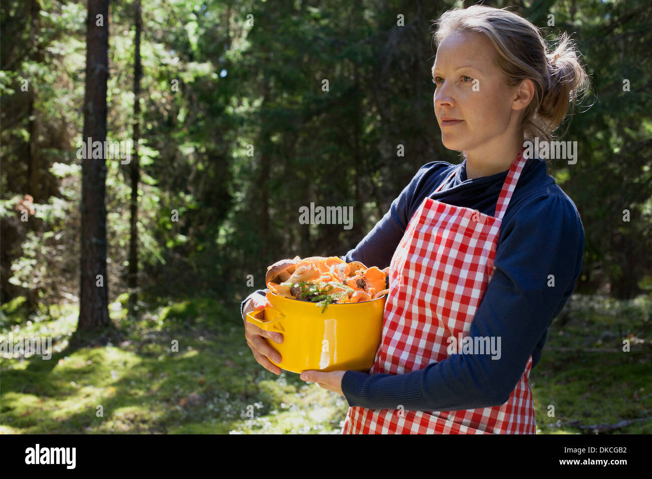 Woman in forest with mushrooms in saucepan Stock Photo