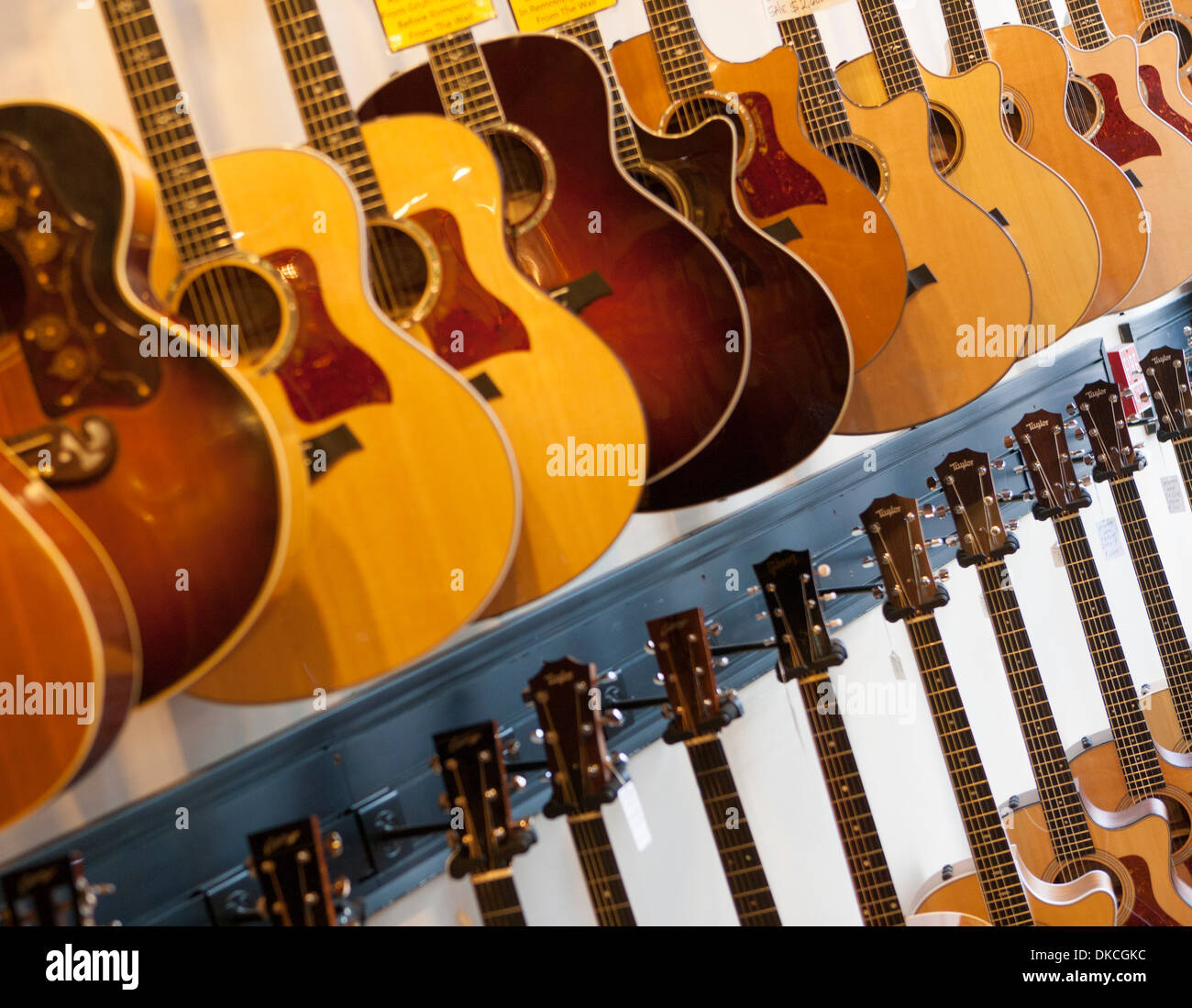 Many used acoustic guitars for sale in a shop - Stock Image
