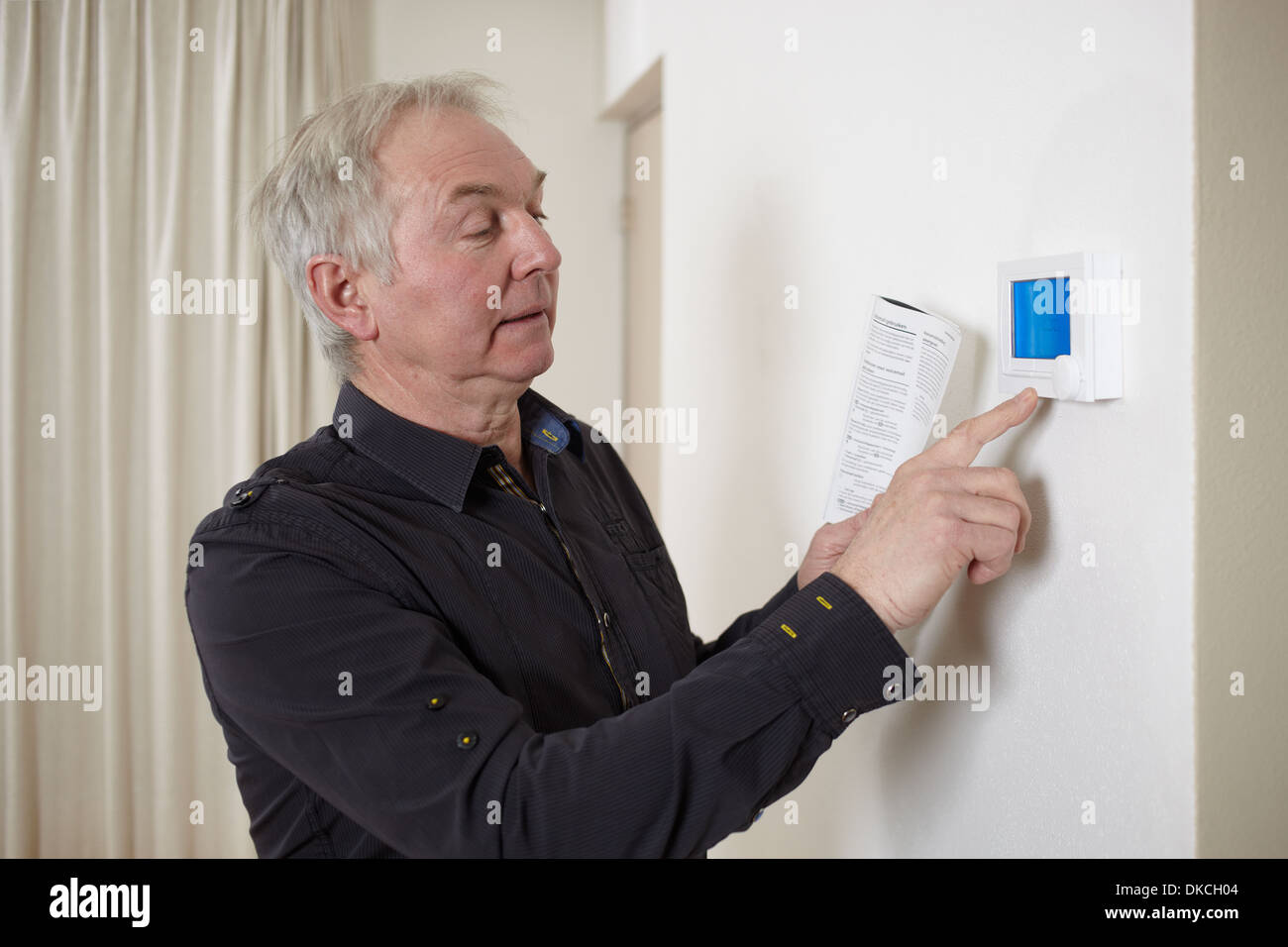 Senior man at home adjusting heating control panel - Stock Image