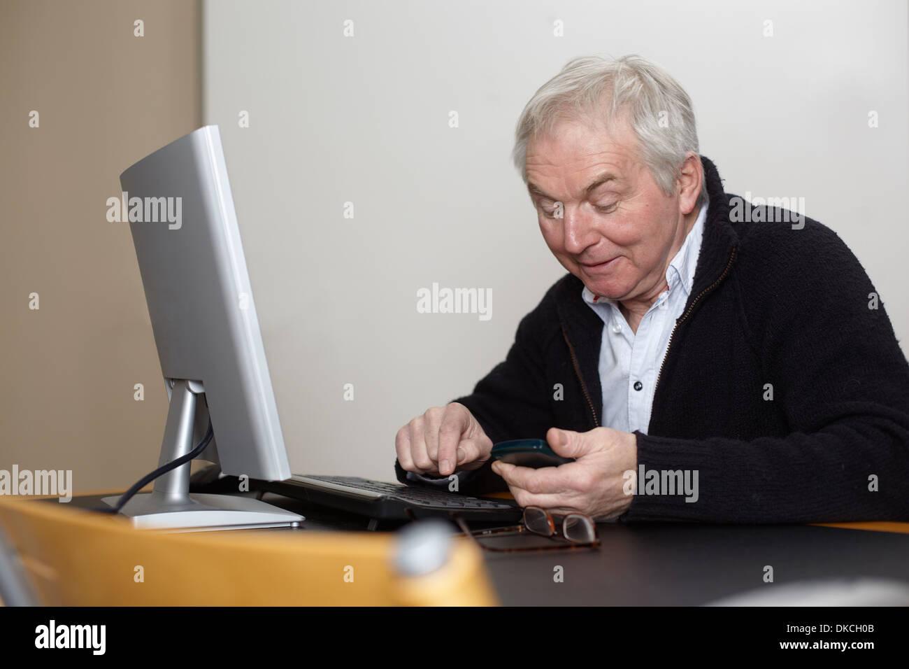 Senior man at home using personal computer - Stock Image