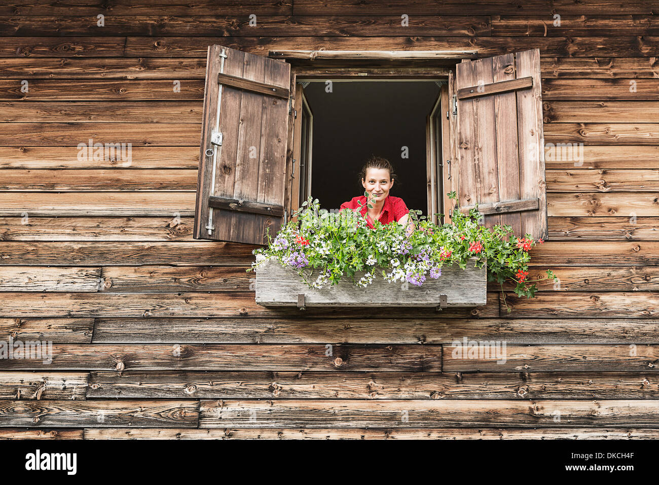 Portrait of mid adult woman at chalet window, Achenkirch, Tyrol, Austria - Stock Image