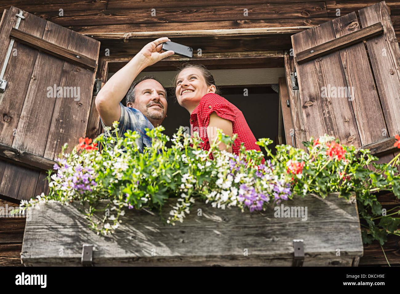 Couple taking self portrait from chalet window, Achenkirch, Tyrol, Austria - Stock Image