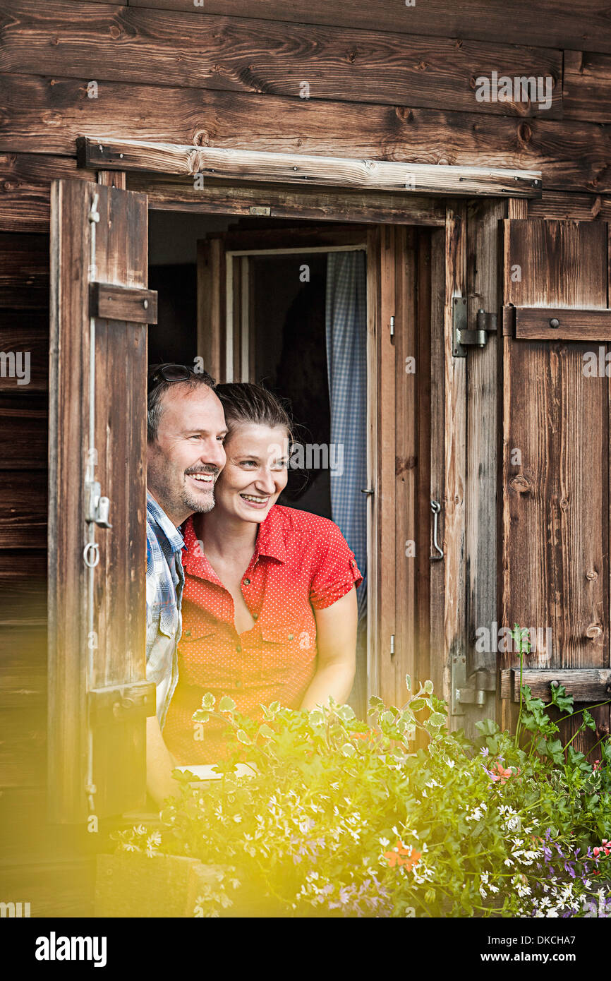 Couple looking out from chalet window, Achenkirch, Tyrol, Austria - Stock Image