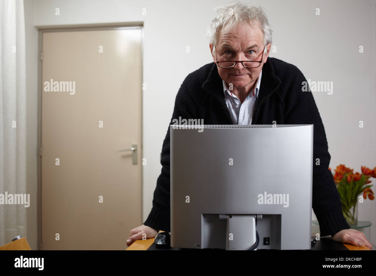 Senior man at home standing in front of personal comuter - Stock Image